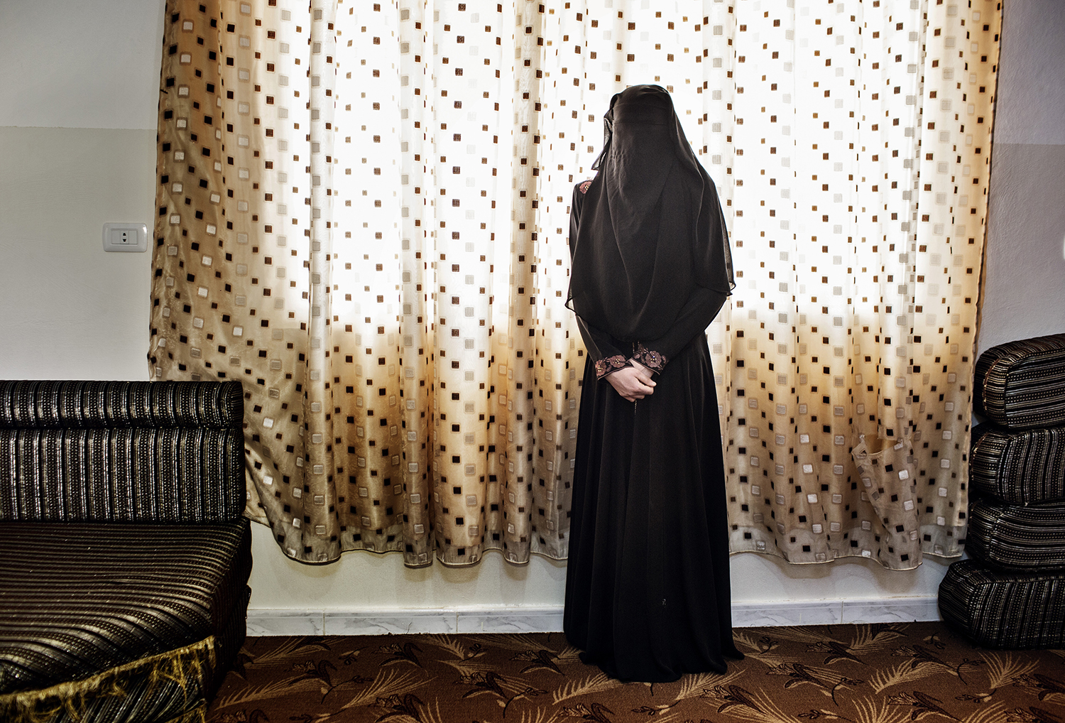 From the series: Tomorrow There Will Be Apricots, on Syrian widows and their families in Jordan.                               M, 15, standing in the niqab she recently started wearing. Her 17-year-old sister had just married, leaving her alone in the  Martyrs' Wives  house with her widowed mother and four siblings. She wanted to finish high school and become a teach. 2014.