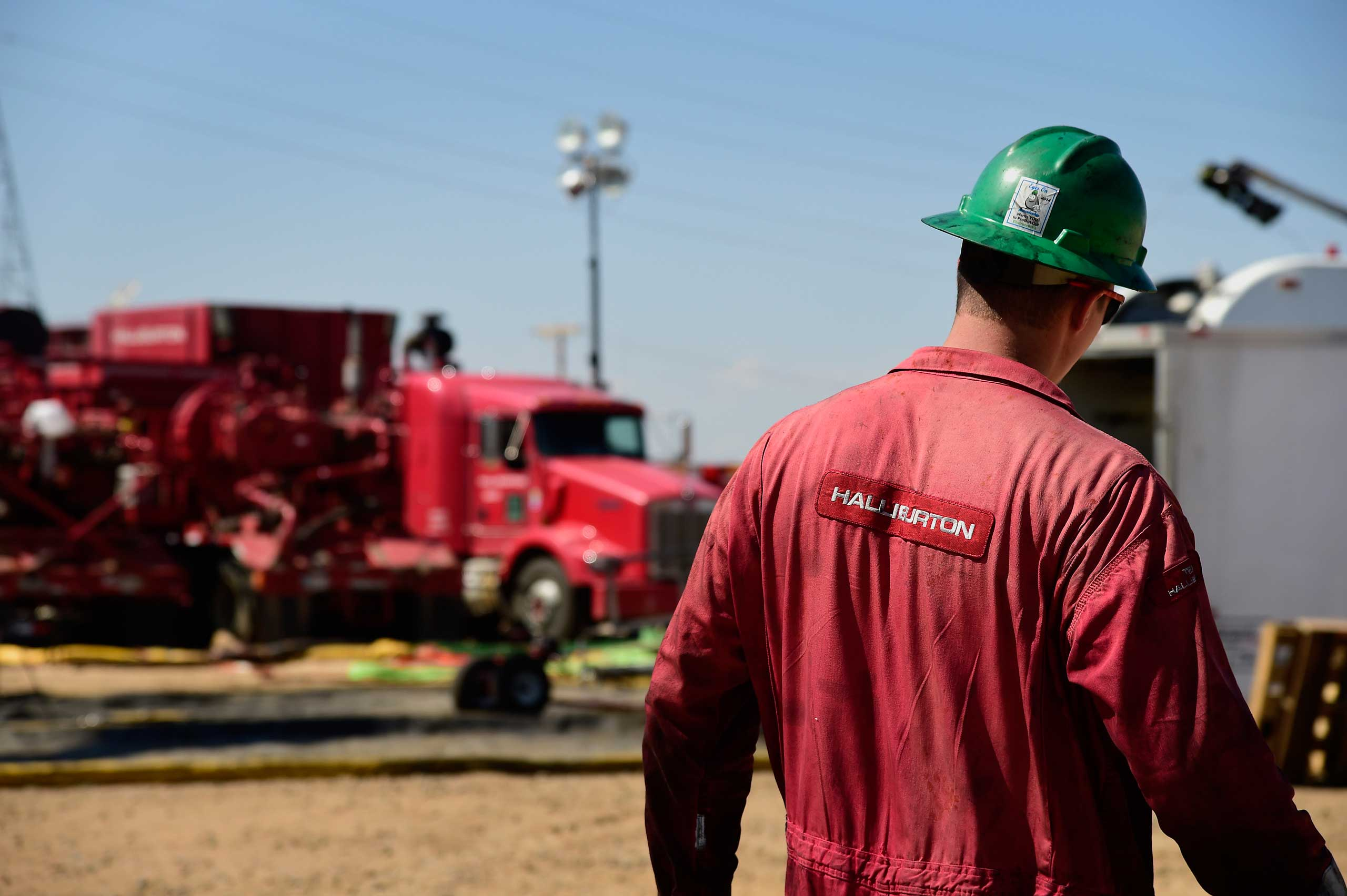 A Halliburton Co. worker walks through an Anadarko Petroleum Corp. hydraulic fracturing (fracking) site north of Dacono, Colo. on Aug. 12, 2014.