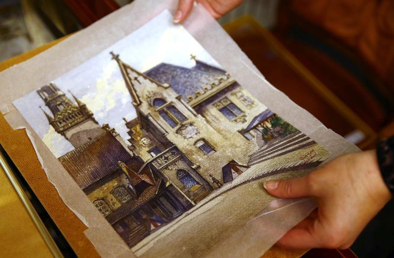 An employee puts away a watercolour of the old registry office in Munich by former German dictator Adolf Hitler at Weidler auction house in Nuremberg November 18, 2014.