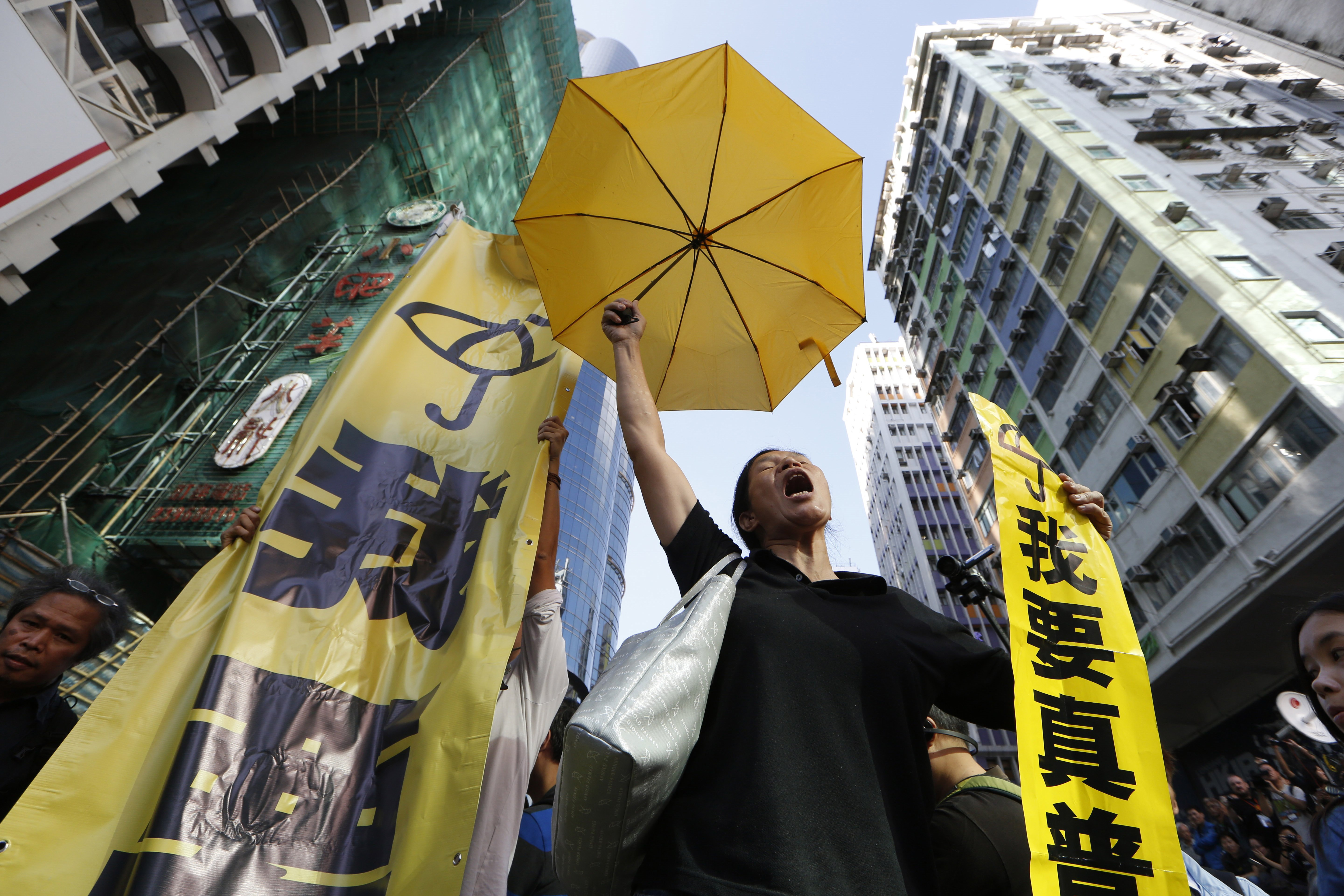 A pro-democracy protester chants at an occupied area before the barricade is removed in Mong Kok district of Hong Kong on Nov. 25, 2014