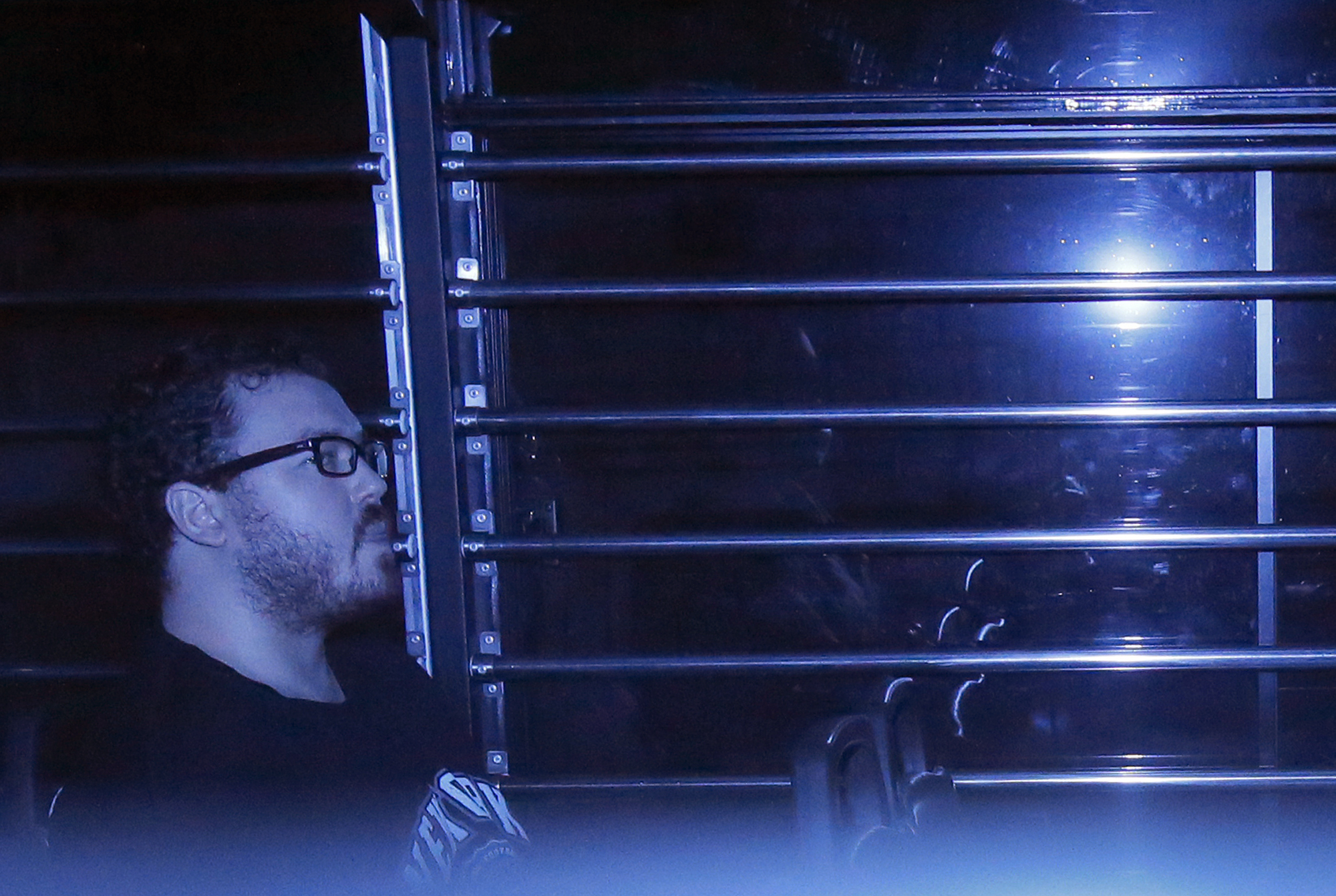 In this photo taken through tinted glass, Rurik George Caton Jutting, a 29-year-old British banker, sits in a prison bus arriving at a court in Hong Kong on Nov. 10, 2014