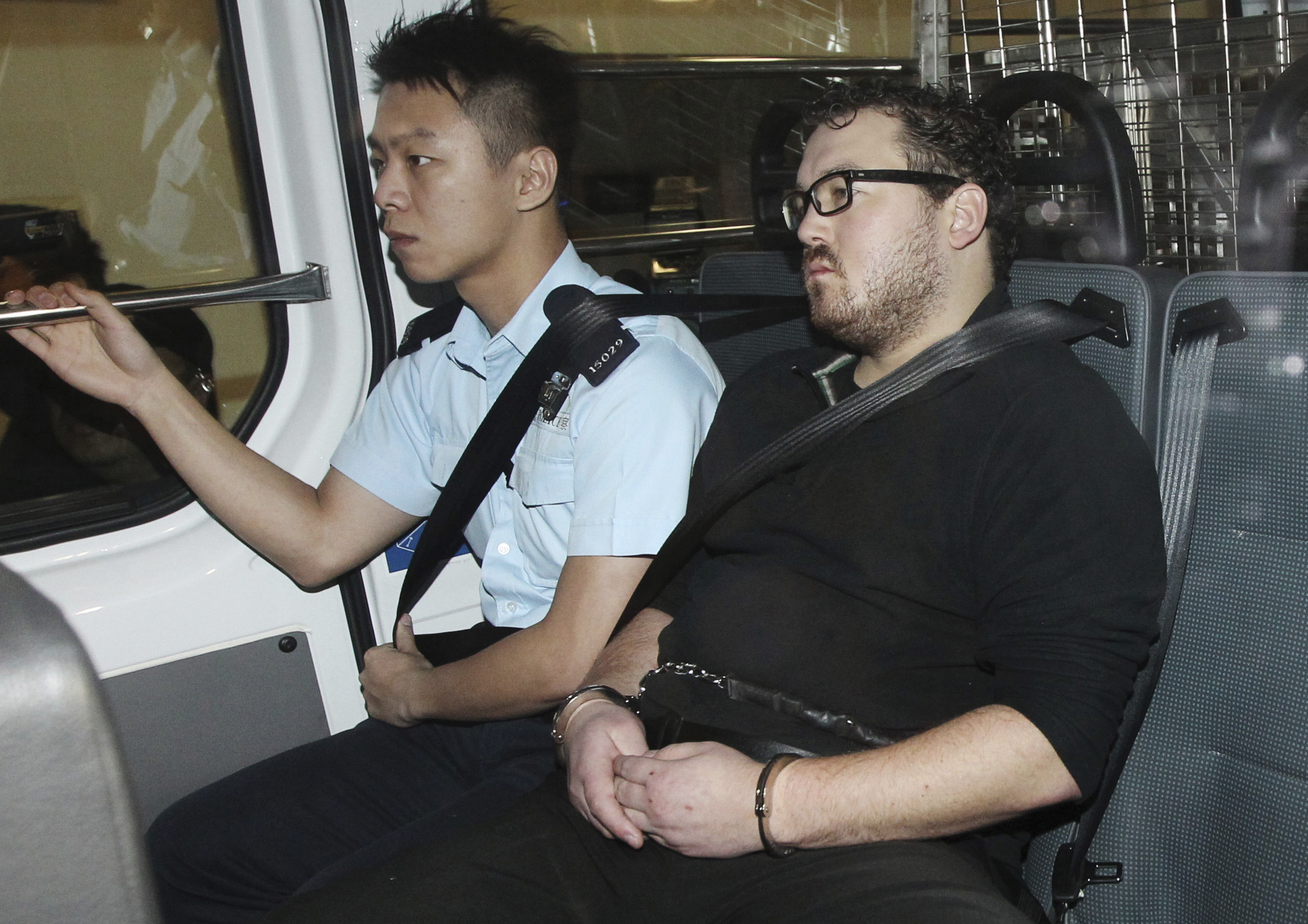 Rurik George Caton Jutting, right, is escorted by a police officer in a police van before appearing in a court in Hong Kong on Nov. 3, 2014