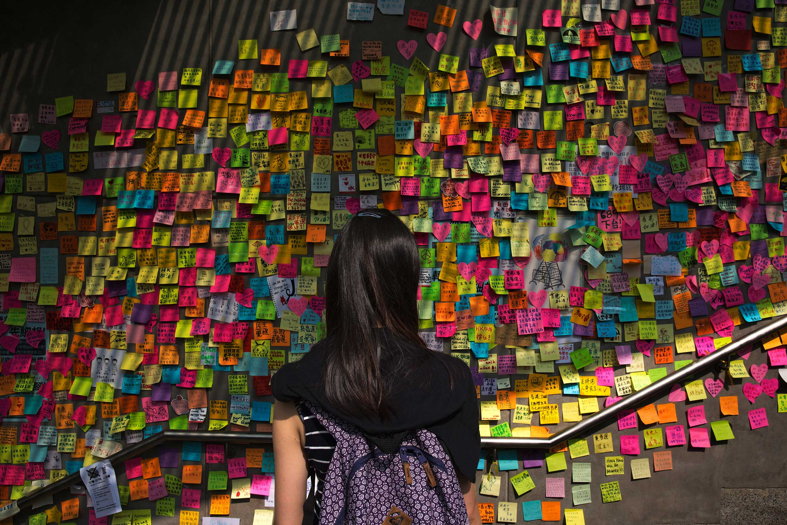 Oct. 4, 2014. A young woman pauses to read messages of encouragement, thoughts, and demands left by protesters near the government offices in Hong Kong. Tens of thousands of pro-democracy demonstrators have occupied central Hong Kong for nine days now. The unprecedented protests continue as the government and demonstrators remain in a stalemate. From  A New Generation Speaks.  October 20, 2014 issue.