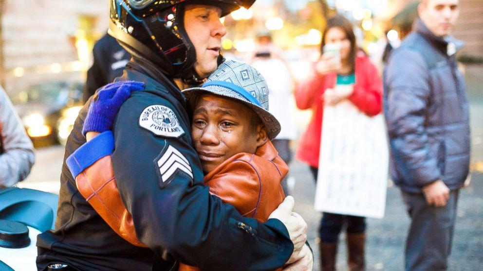 Police Sgt. Bret Barnum hugs 12-year-old Devonte Hart during a demonstration in Portland, Ore., Nov. 25, 2014.