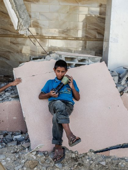 2014.  Gaza.  Palestine. A child with an Israeli mortar shell in a neighborhood destroyed near Rafah in southern Gaza.  Operation Protective Edge lasted from 8 July 2014 – 26 August 2014, killing 2,189 Palestinians of which 1,486 are believed to be civilians. 66 Israeli soldiers and 6 civilians were killed.  It's estimated that 4,564 rockets were fired at Israel by Palestinian militants.