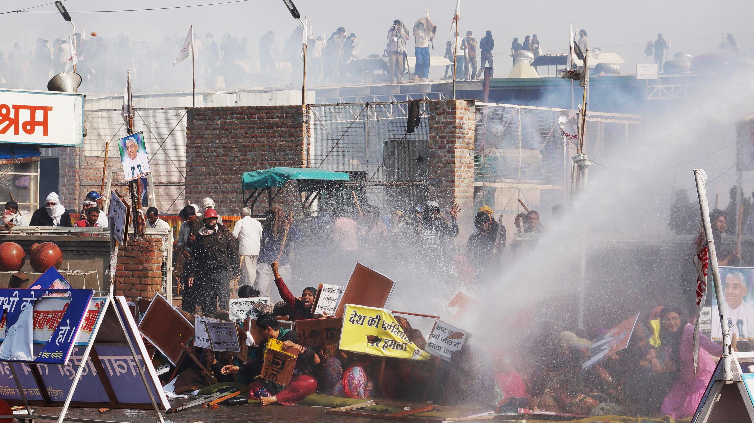 Supporters try to resist police water cannon as police storm the ashram of controversial Indian guru Sant Rampal, in search of him at Hisar in Haryana state, India, Tuesday, Nov.18, 2014.