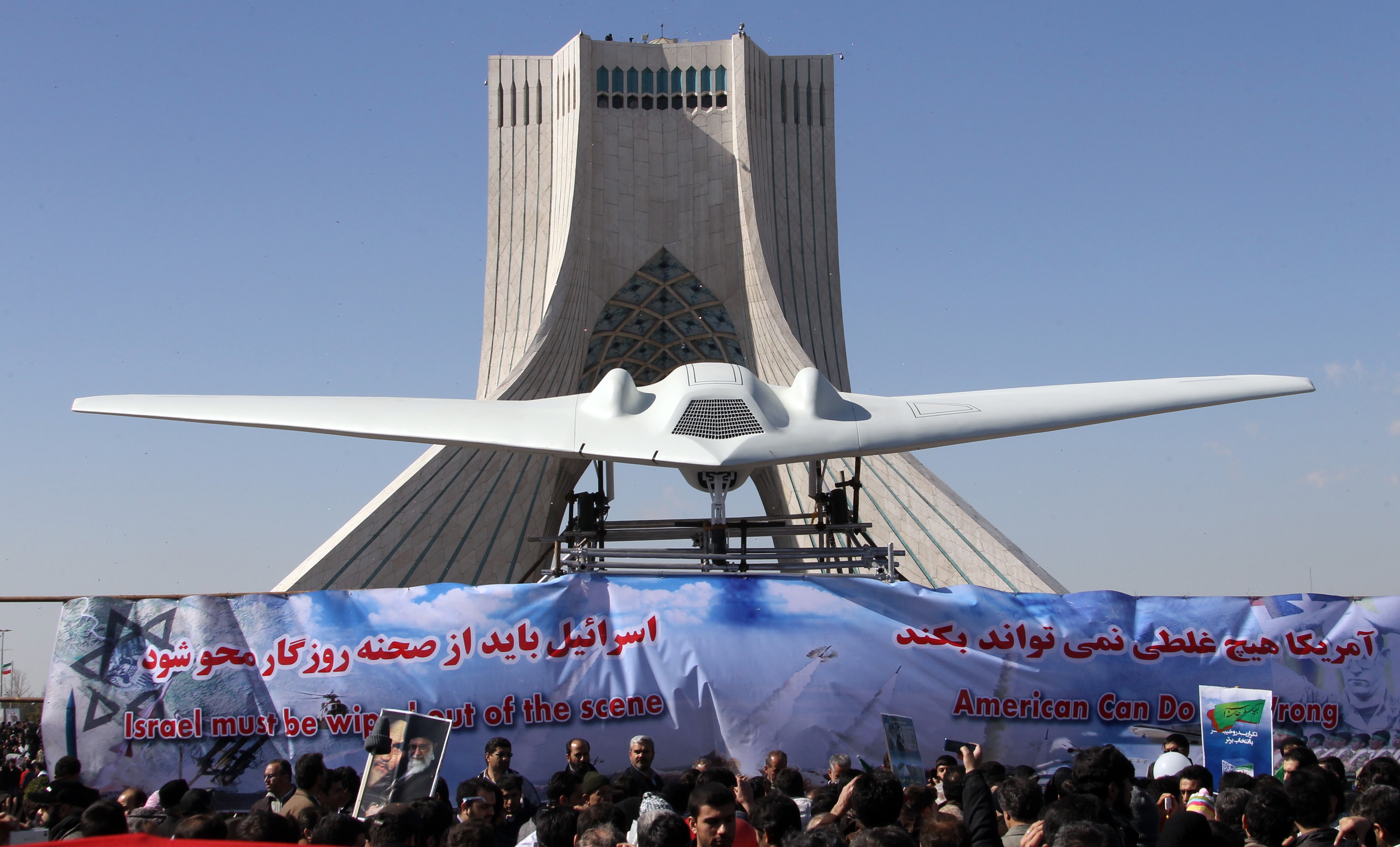 Iranians walk past a replica of the captured US RQ-170 drone which is on display next to the Azadi (Freedom) tower during the 33rd anniversary of the Islamic revolution in Tehran on February 11, 2012.