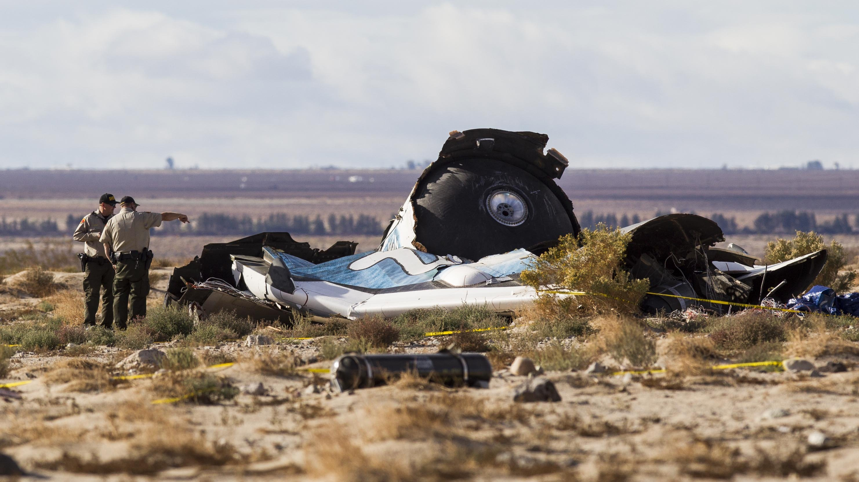 Law enforcement officers take a closer look at the wreckage near the site where a Virgin Galactic space tourism rocket, SpaceShipTwo, exploded and crashed in Mojave, Calif. on Nov 1, 2014.