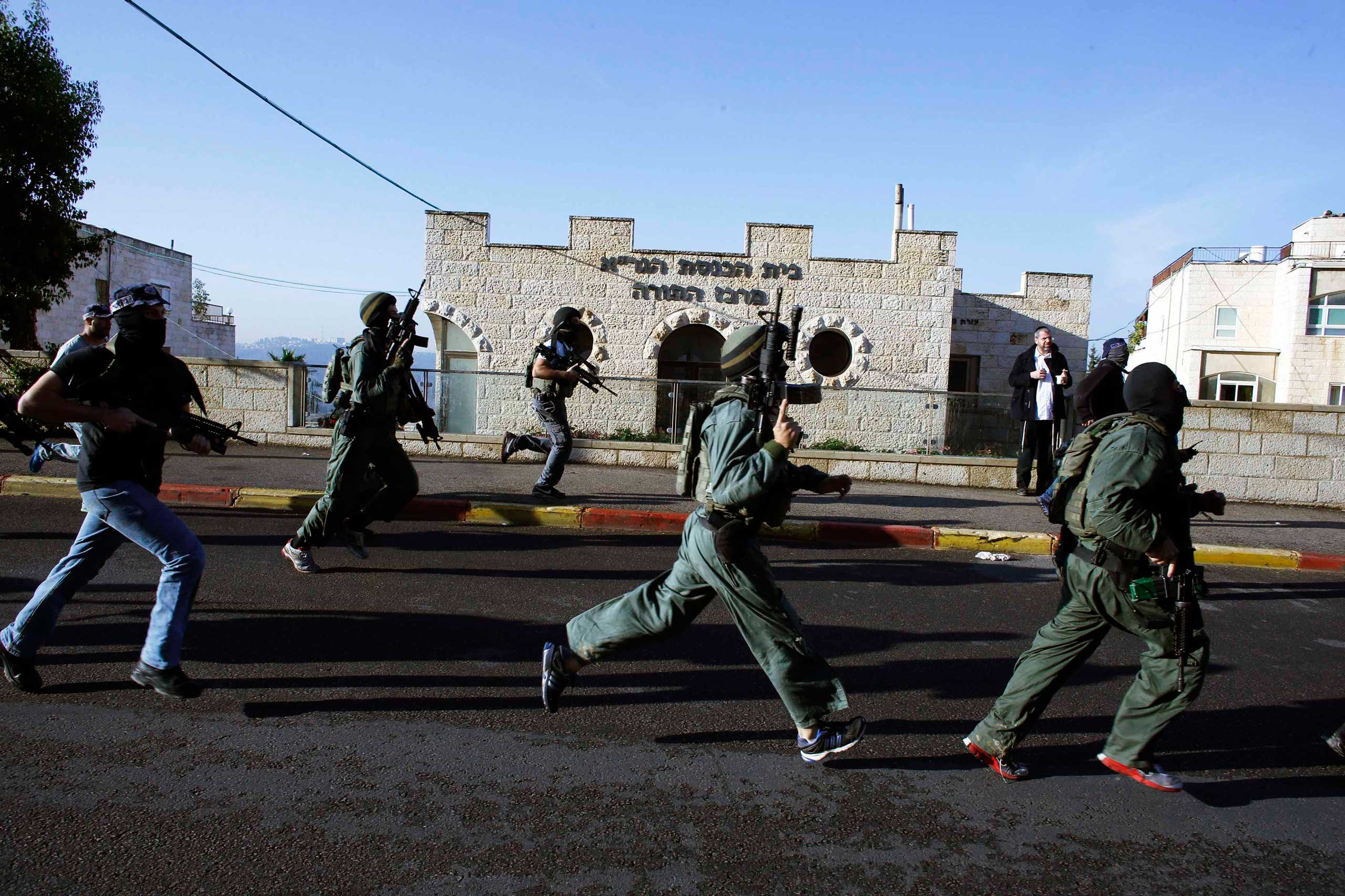 Israeli security personnel run next to a synagogue, where a suspected Palestinian attack took place, in Jerusalem on Nov. 18, 2014.