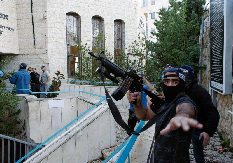 An Israeli police officer gestures as he holds a weapon near the scene of an attack at a Jerusalem synagogue, Nov. 18, 2014.
