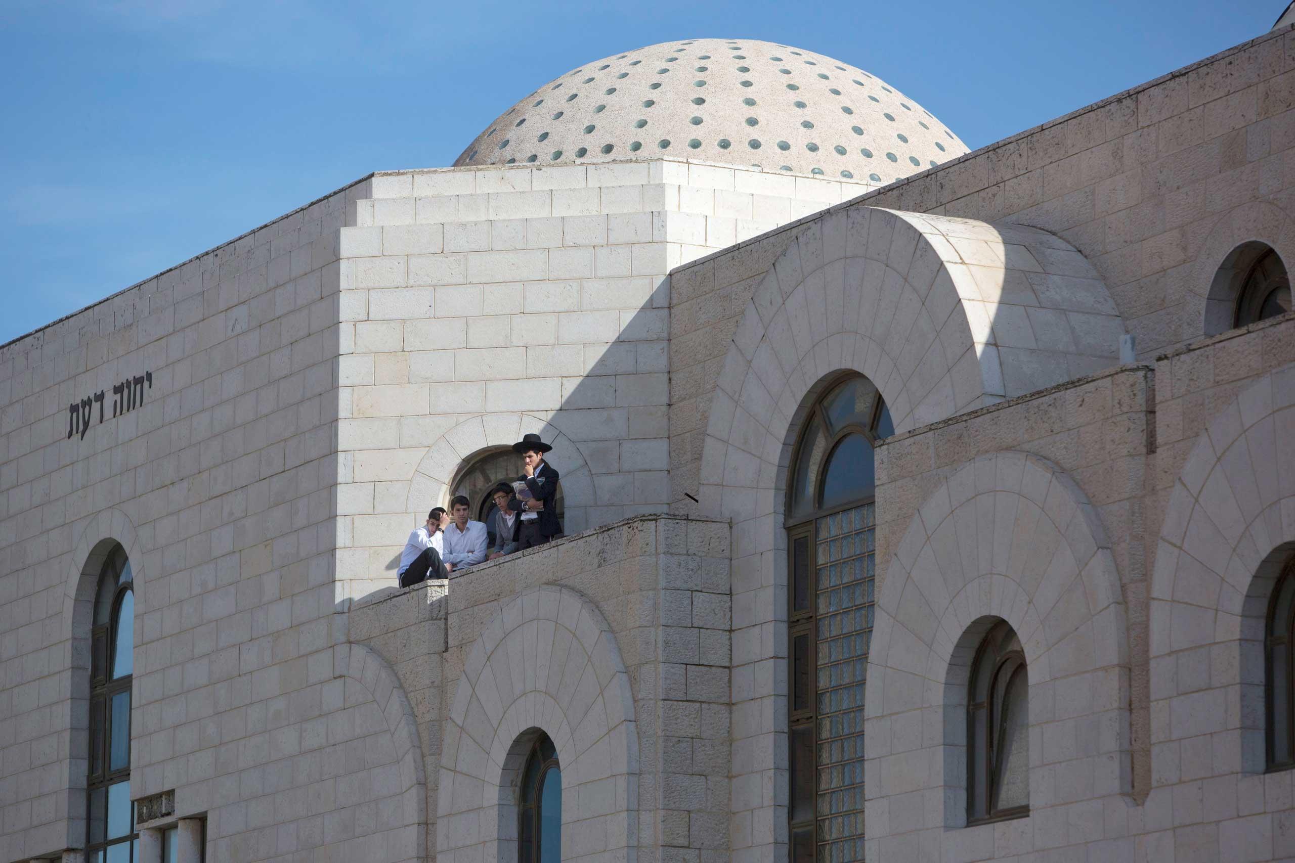 Ultra-Orthodox Jewish boys look at the scene in Jerusalem on Nov. 18, 2014.