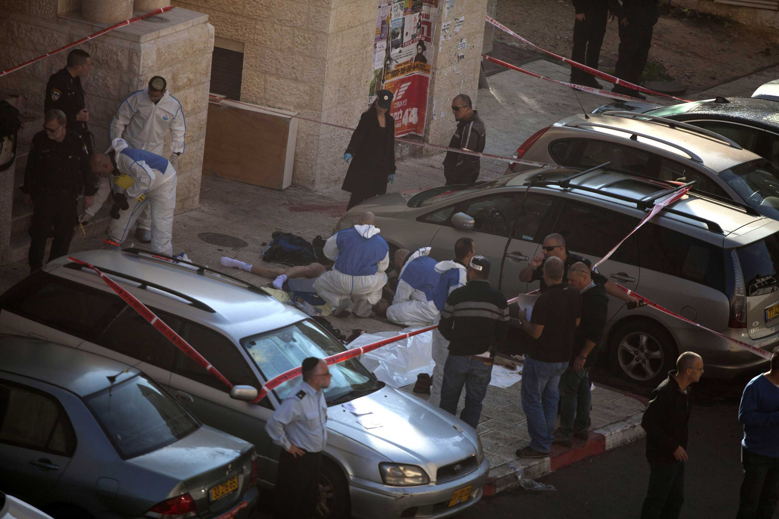 Israeli police crime scene investigators stand near bodies of suspected attackers outside a synagogue in Jerusalem on Nov. 18, 2014.