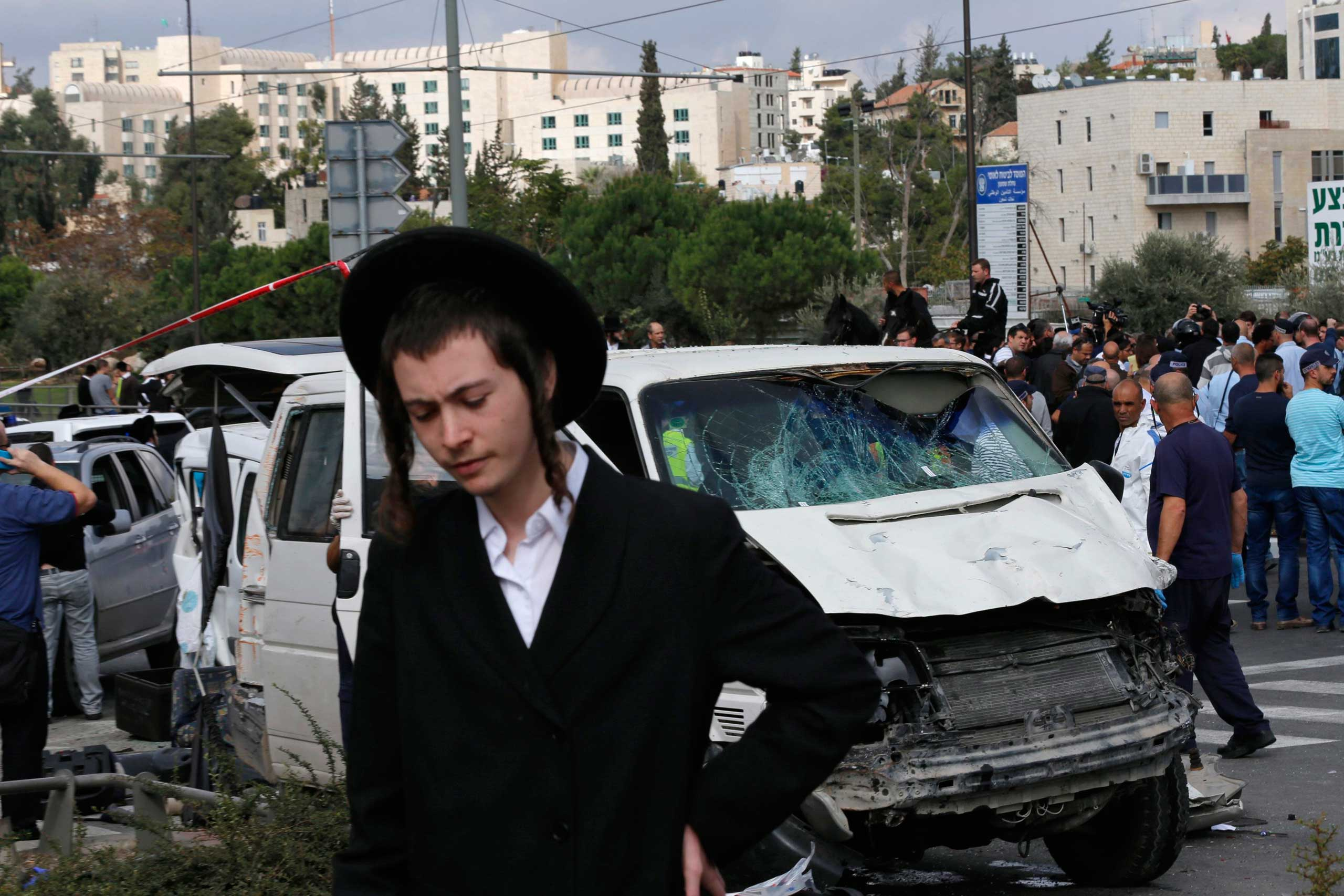 An ultra-Orthodox youth stands in front of the vehicle of a Palestinian motorist who rammed into pedestrians at the scene of an attack in Jerusalem, Nov. 5, 2014.