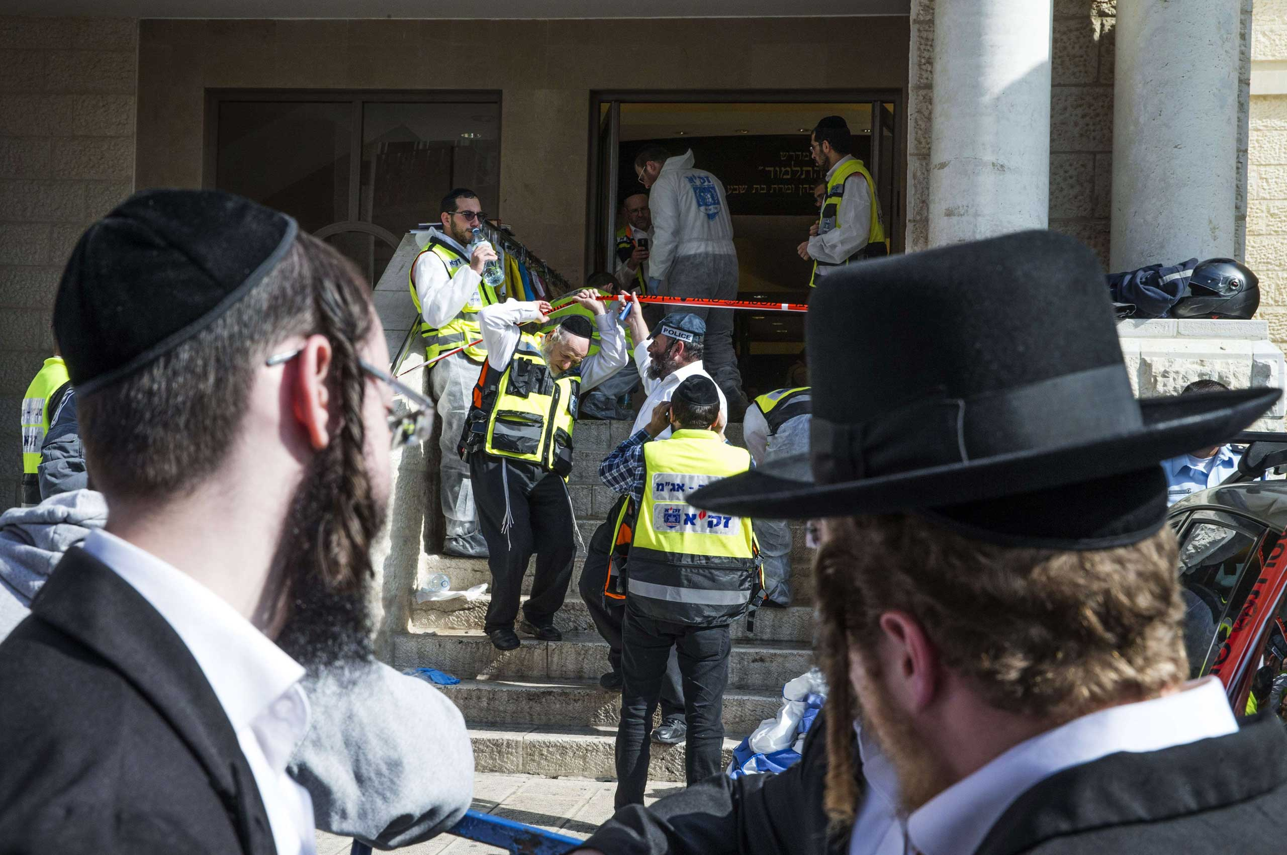Ultra-orthodox Jewish men look on at the scene of an attack on Israeli worshippers at a synagogue in the ultra-Orthodox Har Nof neighborhood in Jerusalem on Nov. 18, 2014.