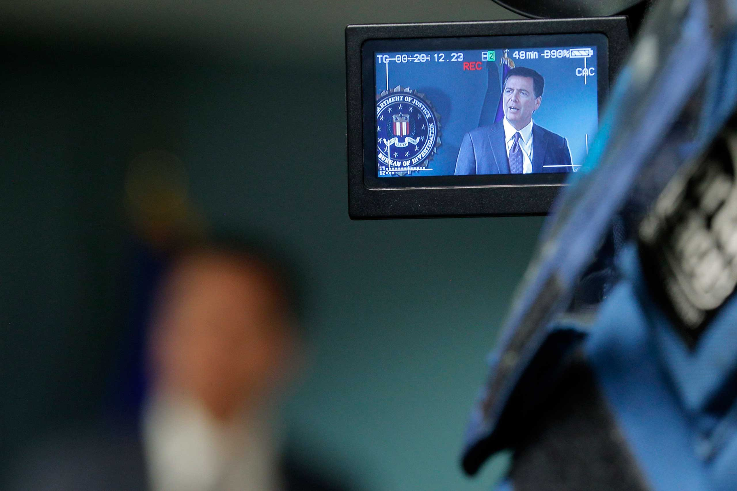 Television cameras record FBI Director James Comey as he answers questions from reporters during a news conference at the FBI office in Boston, Mass., Nov. 18, 2014.