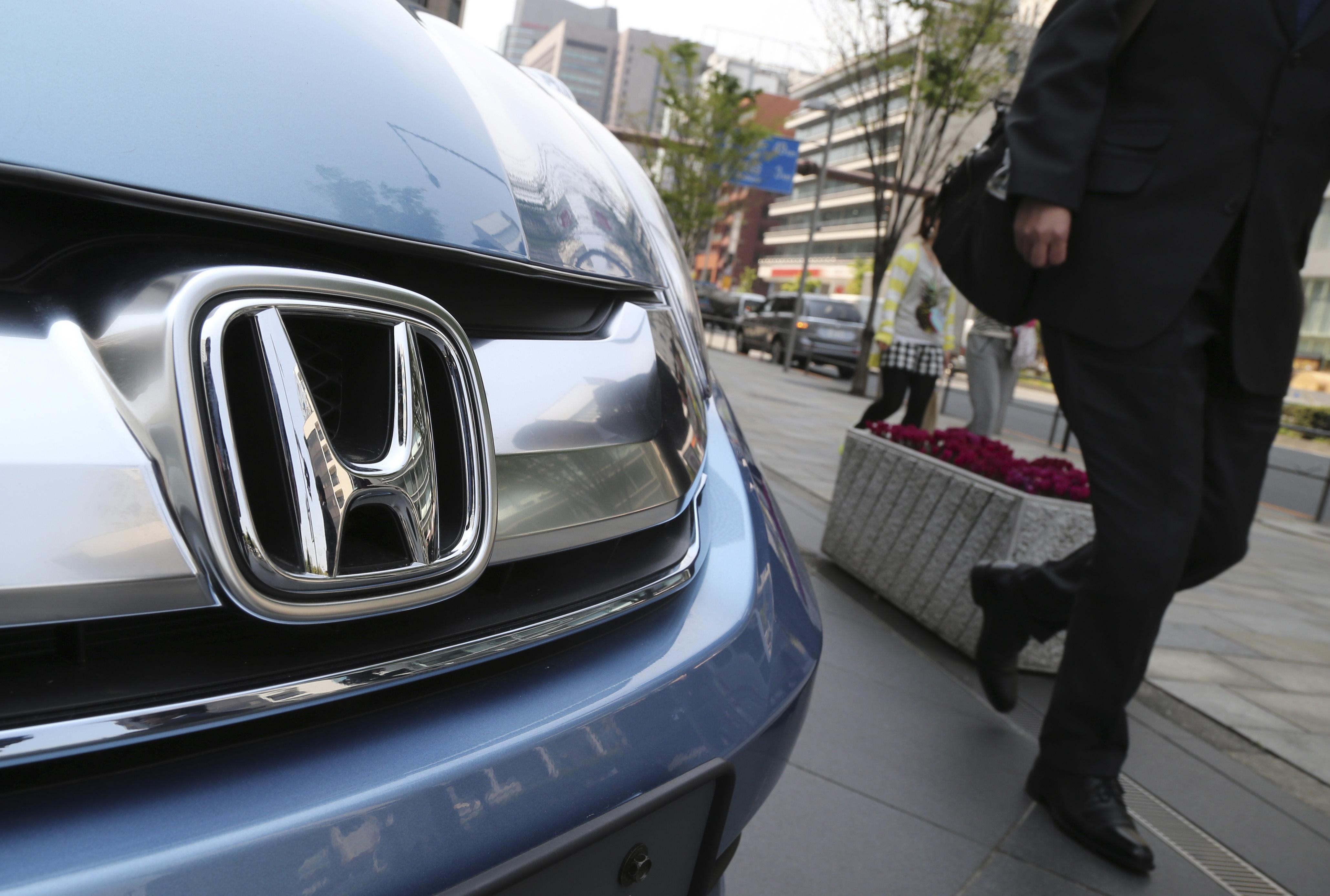 A man walks past a Honda model on display at Honda Motor Co. headquarters in Tokyo on April 25, 2014.