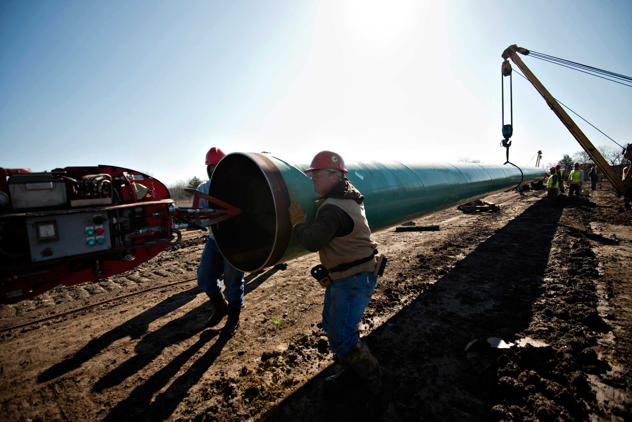 Workers move a section of pipe during construction of the Gulf Coast Project pipeline, part of the Keystone XL Pipeline Project, in Atoka, Okla. on March 11, 2013.