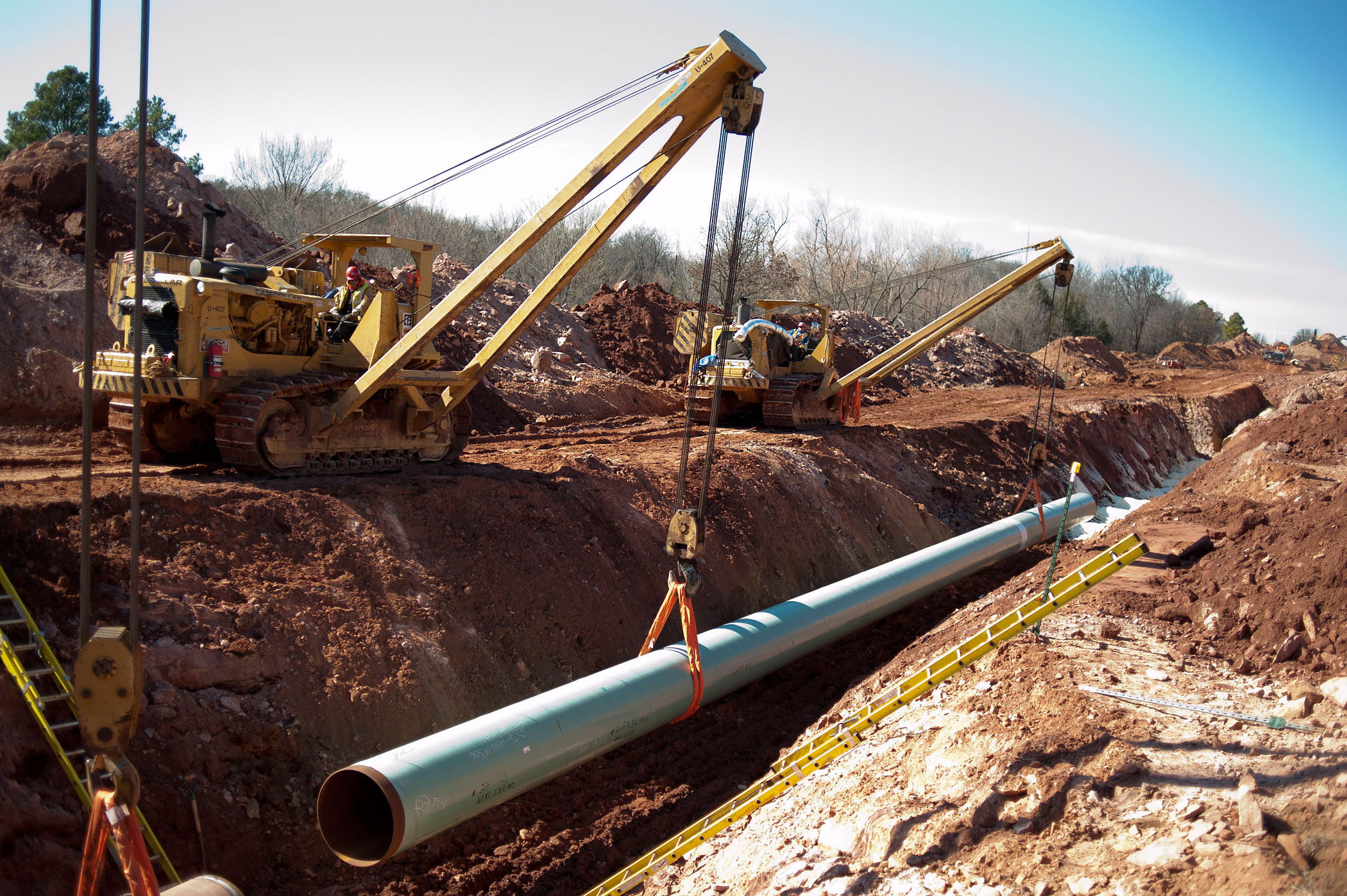 A sixty-foot section of pipe is lowered into a trench during construction of the Gulf Coast Project pipeline in Prague, Oklahoma, U.S., on March 11, 2013.