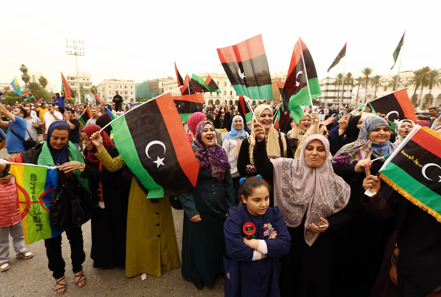 Libyans wave the national flag as they gather at Martyrs' Square to celebrate the decision of Libya's supreme court, in Tripoli on November 6, 2014.