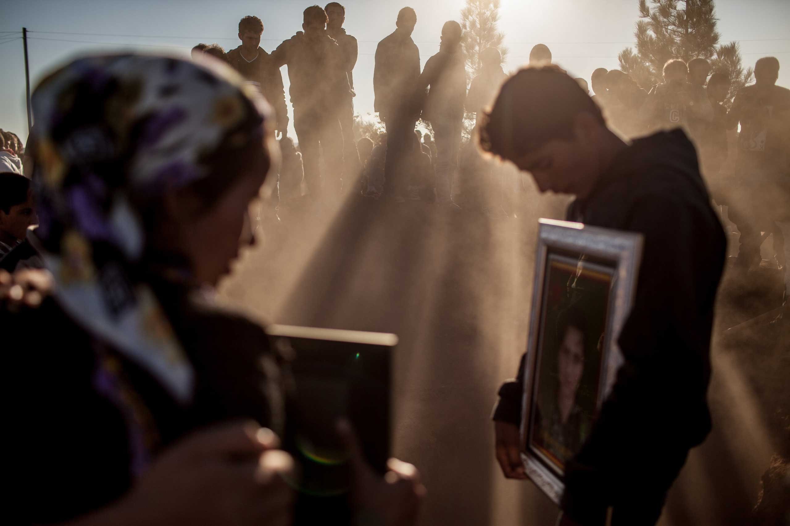 Nov. 7, 2014. Kurdish mourners bury two female fighters from YPJ (Women's protection Force),  killed during fighting against Islamiic State Militants, in the border town of Surac, Turkey.
