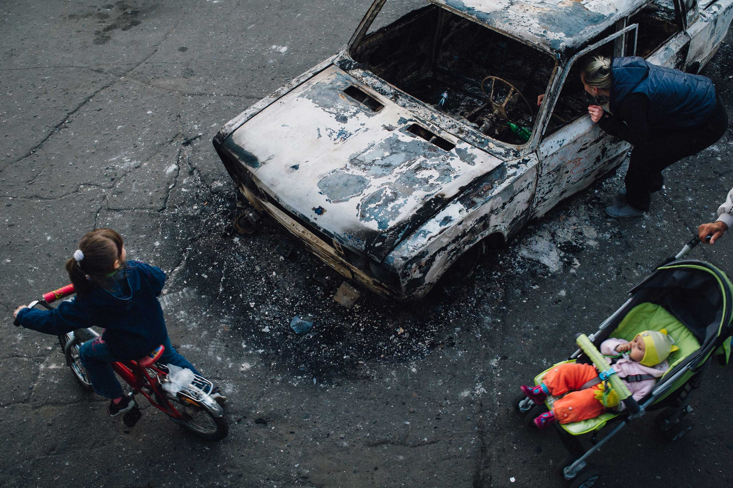 May 3, 2014. Local citizens gather near destroyed vehicles that were burned by pro-Russian separatists in Kramatorsk, in eastern Ukraine. From  This is War.  May 19, 2014 issue.