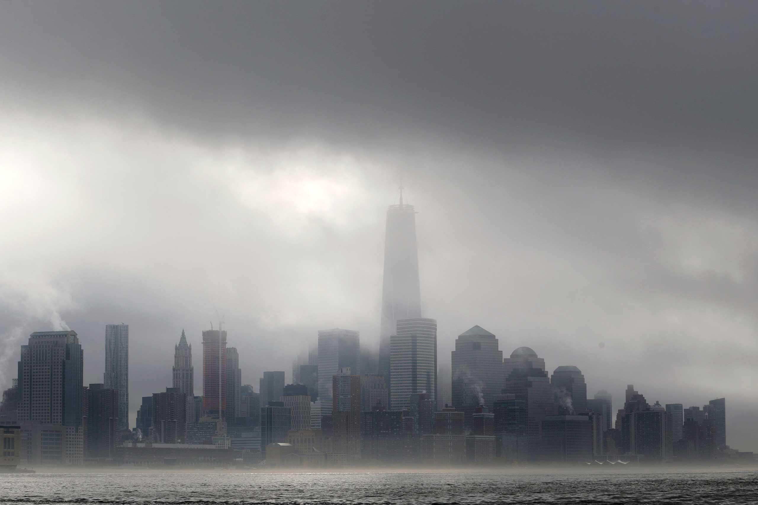 Heavy fog blankets lower Manhattan in New York, including One World Trade Center, center, in this view across the Hudson River from Hoboken, N.J., Nov. 12, 2014.