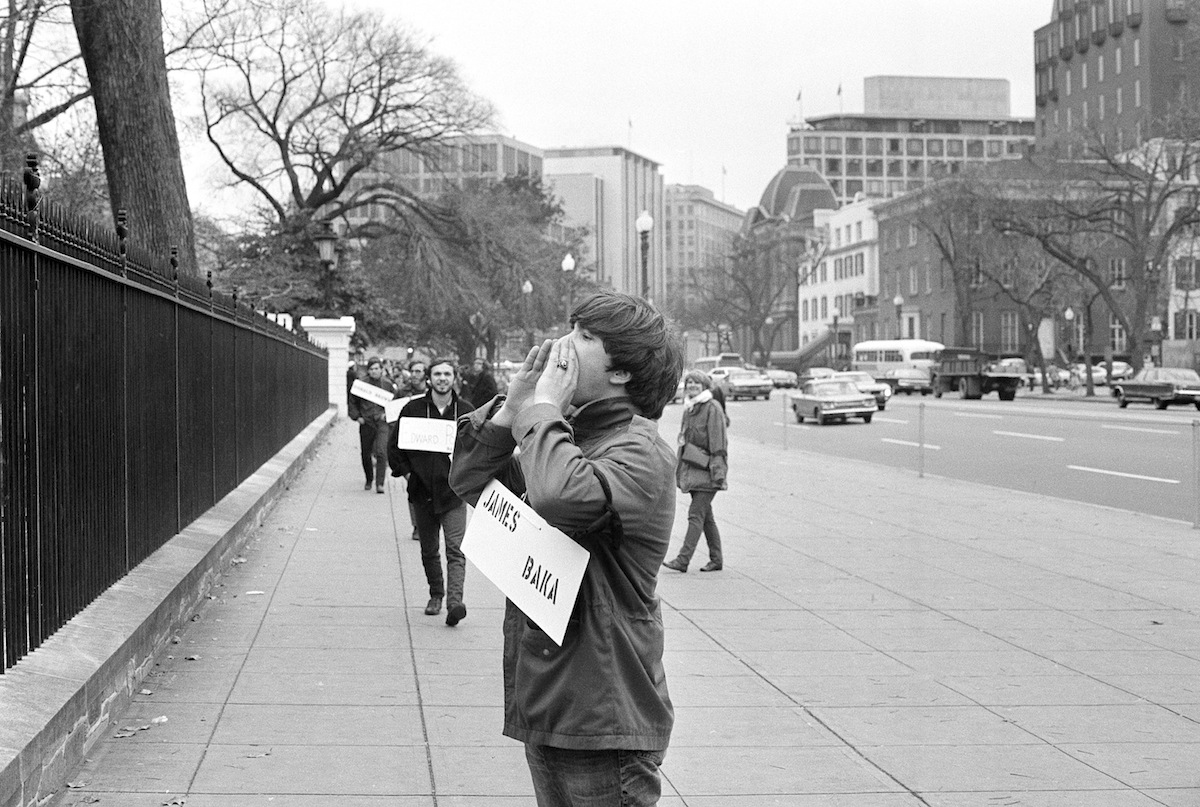 Wearing the name of a serviceman who died in Vietnam, a marcher pauses in front of the White House on Nov. 14, 1969