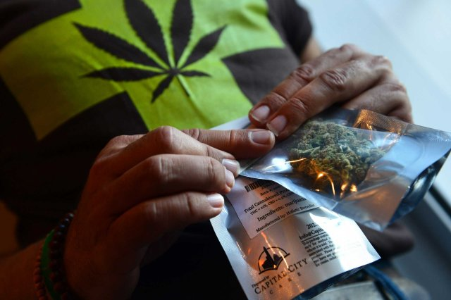 A man purchases medical marijuana, the first legal sale, at Capital City Care in Washington, D.C., on July 29, 2013.