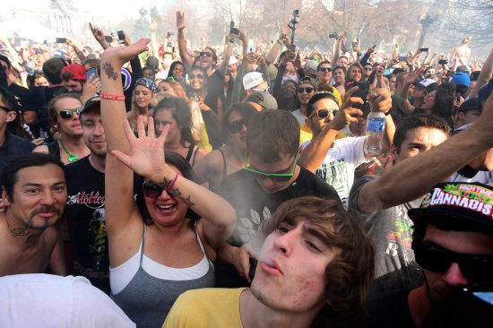 Hundreds of people light up joints, bongs, pipes and marijuana cigarettes at exactly 4:20 pm during the Colorado 420 Rally at Civic Center Park in Denver on April 20, 2014.