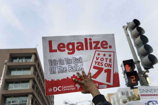 A man holds up a sign for Ballot Initiative #71, the legalization of marijuana, in Washington, D.C., on Nov. 4, 2014.