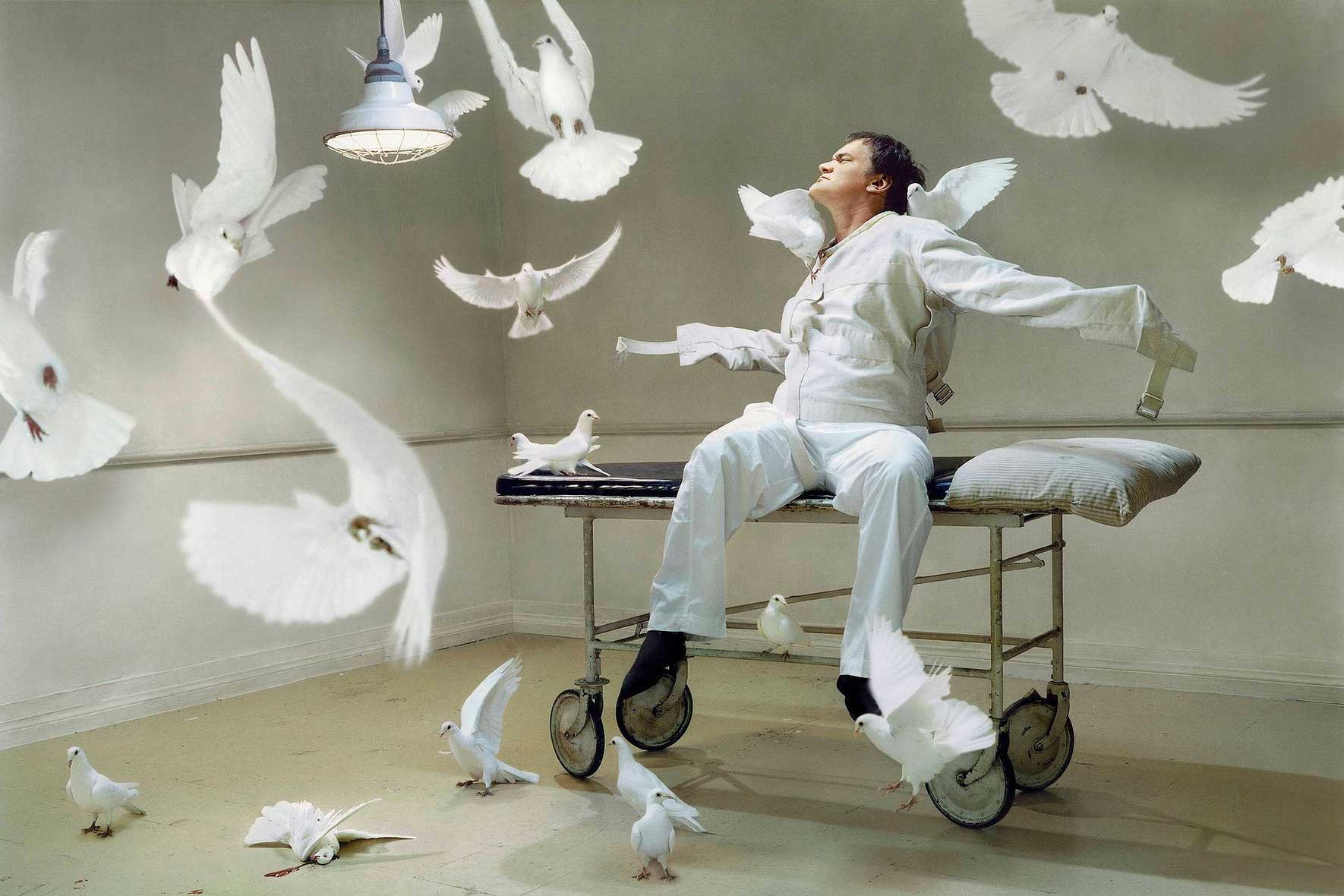 Quentin Tarantino.                                                               This was during the days of Kill Bill. I thought of a shoot with white doves. Sort of him being the victim of these white doves -- a [symbolic] mixture of One Flew Over the Cuckoos Nest, and the symbol of peace. We had the doves and the gurney and it took a while to talk him into it. There were dove wranglers and [the doves] would fly around and come back. Not all the doves are in this frame, though. There is one dead one which makes the whole thing slightly more sinister.