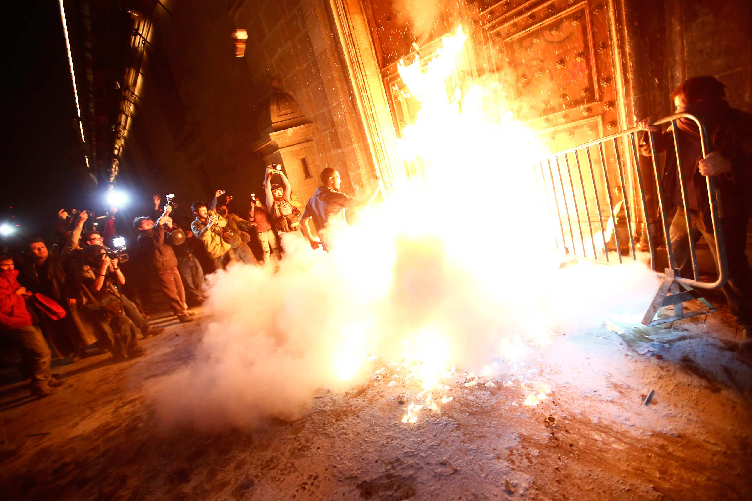 A group of protesters set fire to the wooden door of Mexican President Enrique Pena Nieto's ceremonial palace, during a protest in Mexico City, November 8, 2014.
