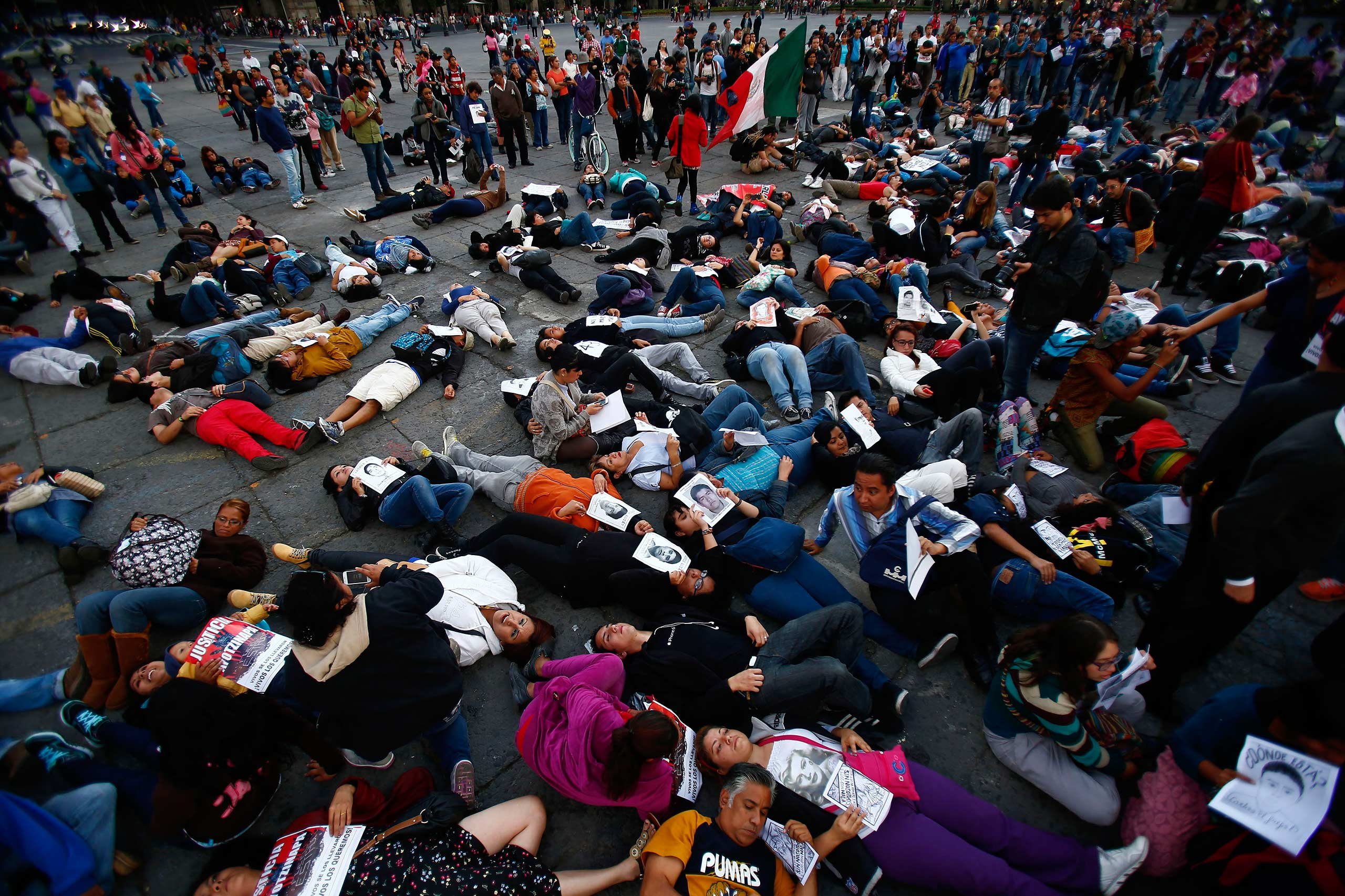 Demonstrators lie on the floor during a protest at Zocalo square in Mexico City November 8, 2014.