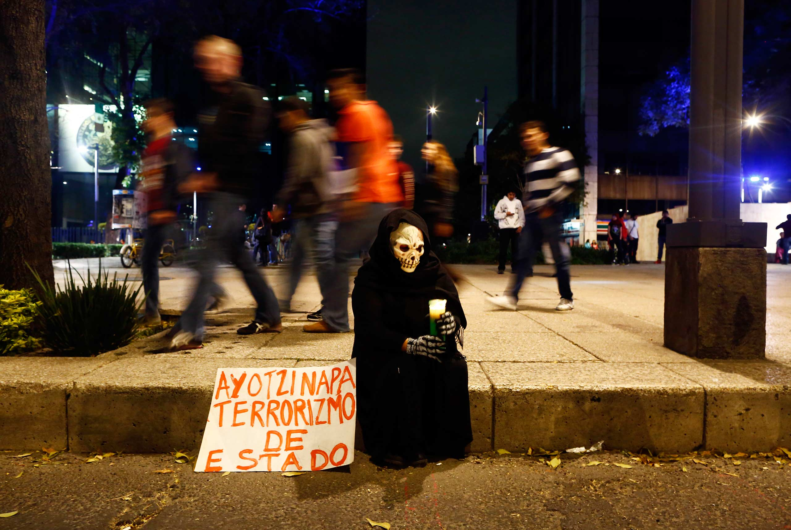 A person in a disguise sits on a sidewalk holding a candle during a protest in Mexico City on November 8, 2014.