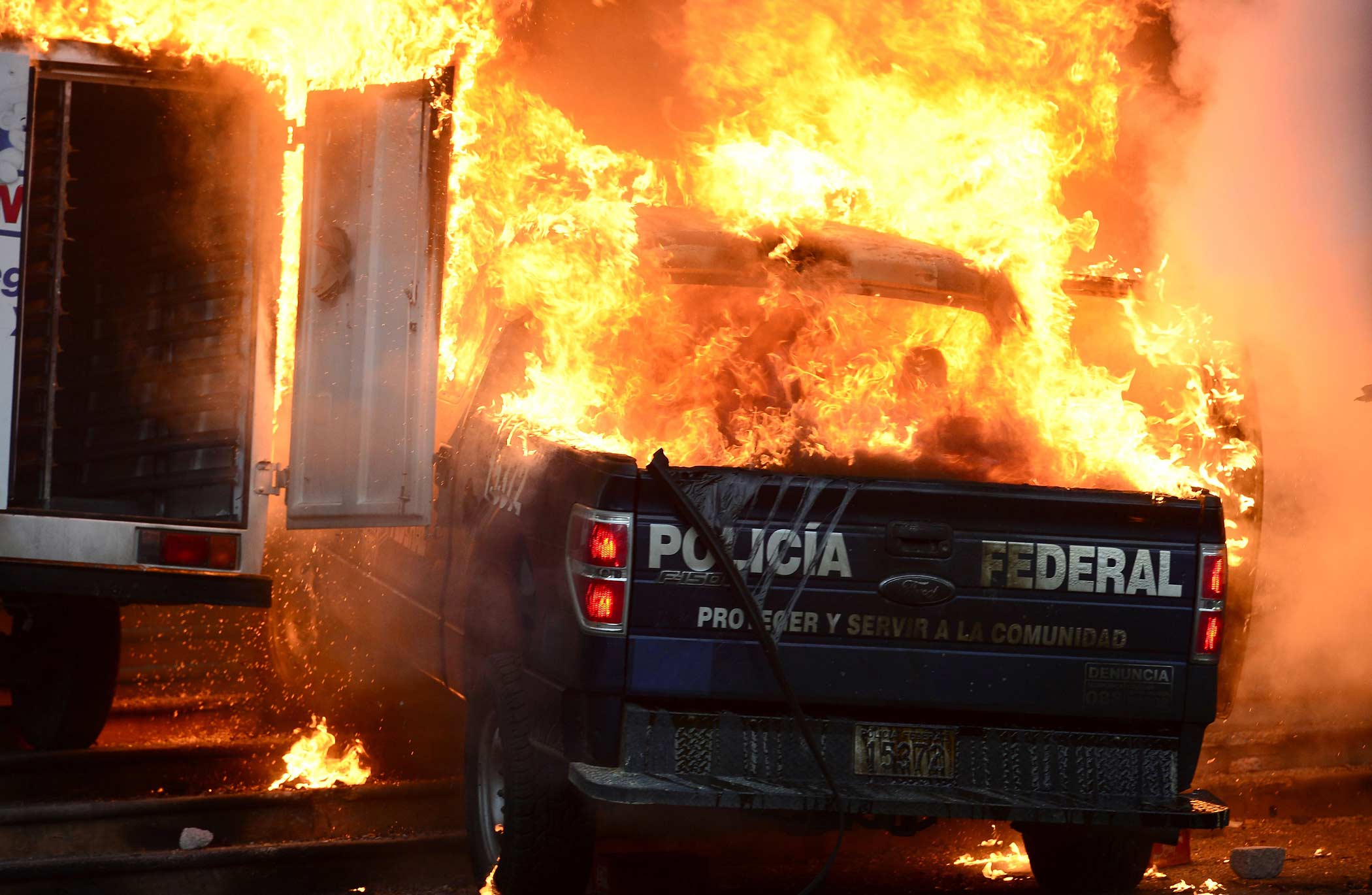 Burning cars are seen during a protest demanding for justice in the case of the 43 missing students, outside the State Government headquarters in Chilpancingo, Guerrero State, on November 8, 2014.