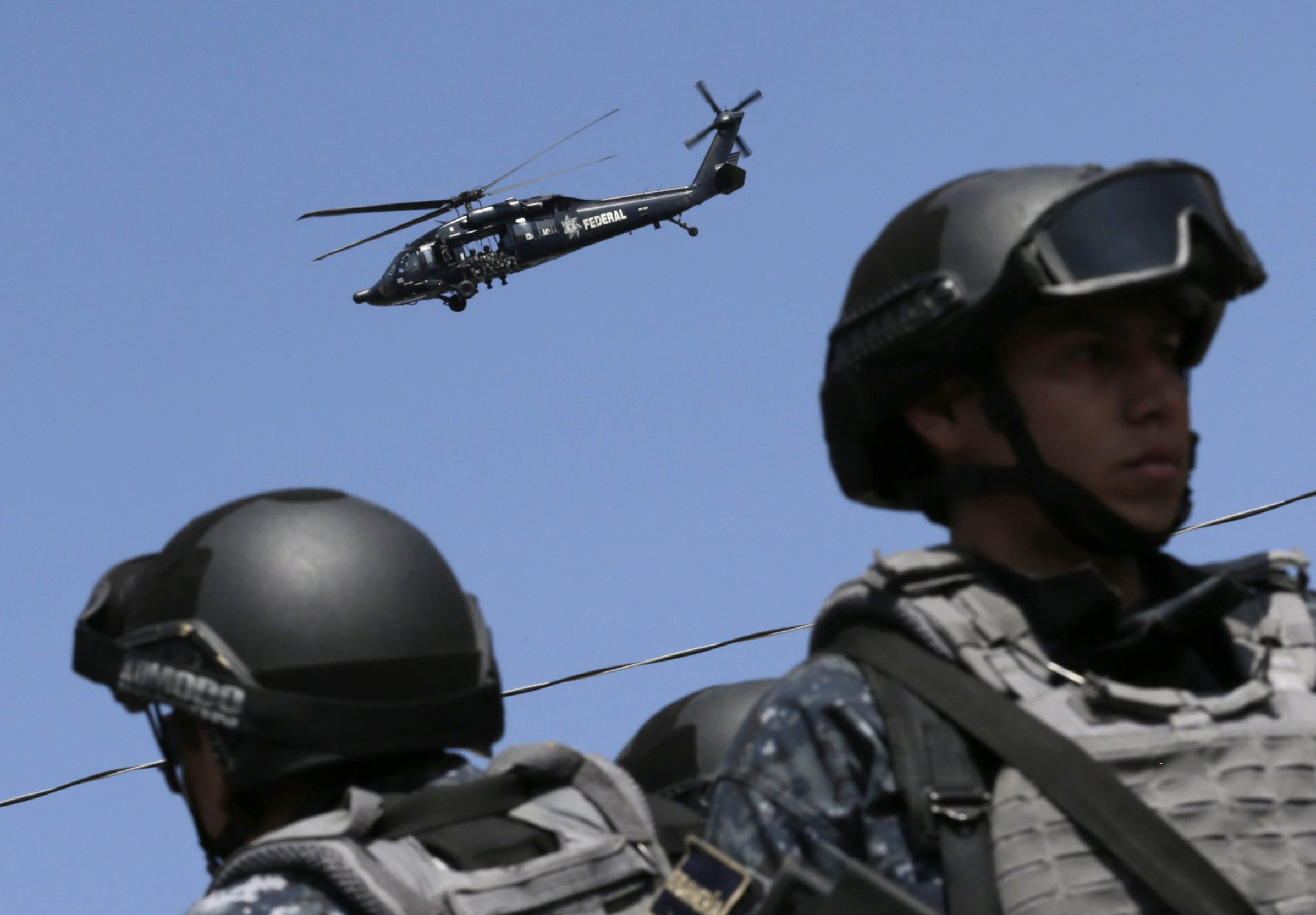 Federal police and a helicopter search for the missing 43 students of the Ayotzinapa Teacher Training College Raul Isidro Burgos are seen in Tianquizolco, near Cocula, Mexico on Nov. 7, 2014.