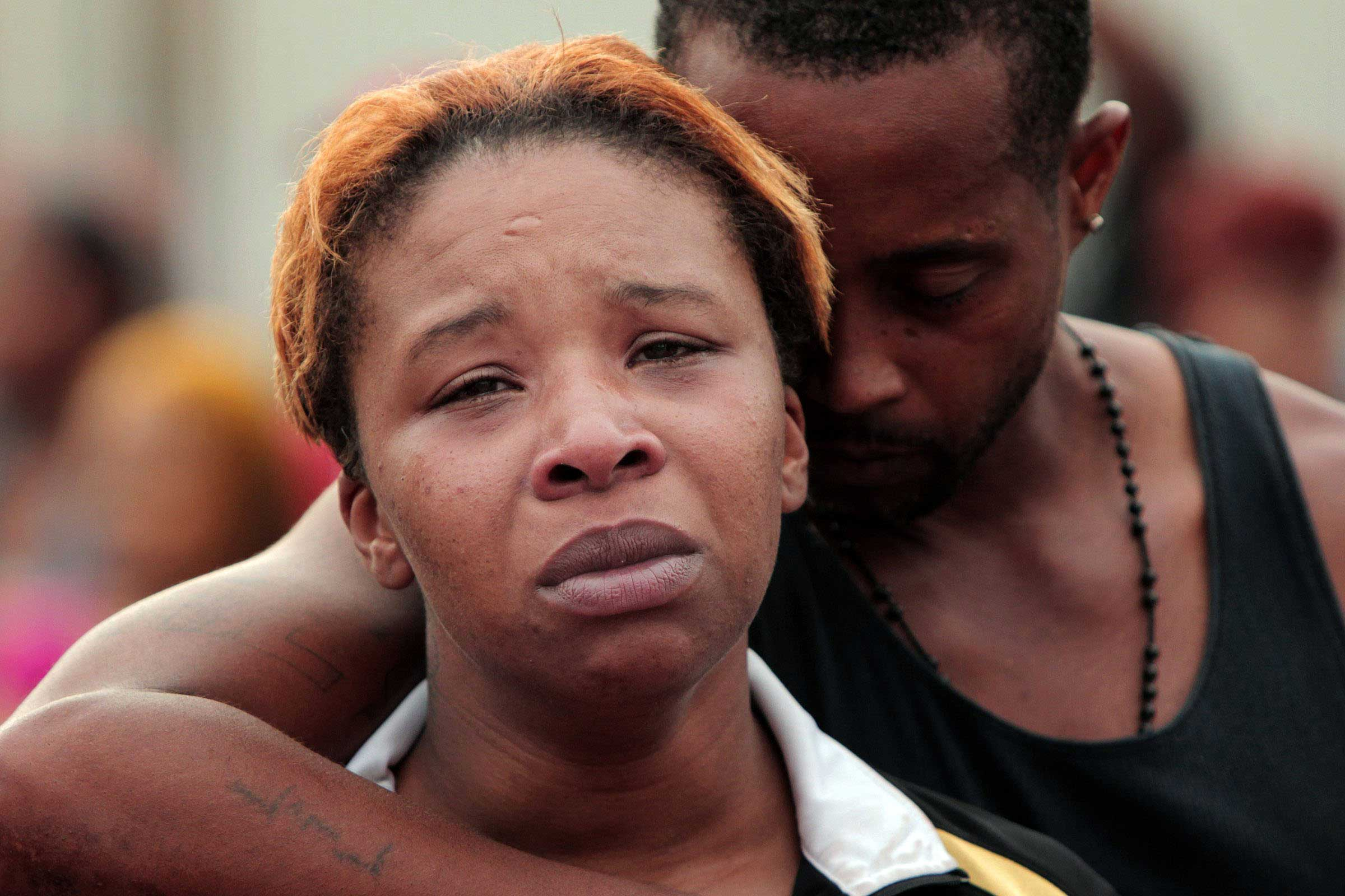 Lesley McSpadden, Brown's mother, is comforted by her husband, Louis Head, on Aug. 9, 2014, after her son's death