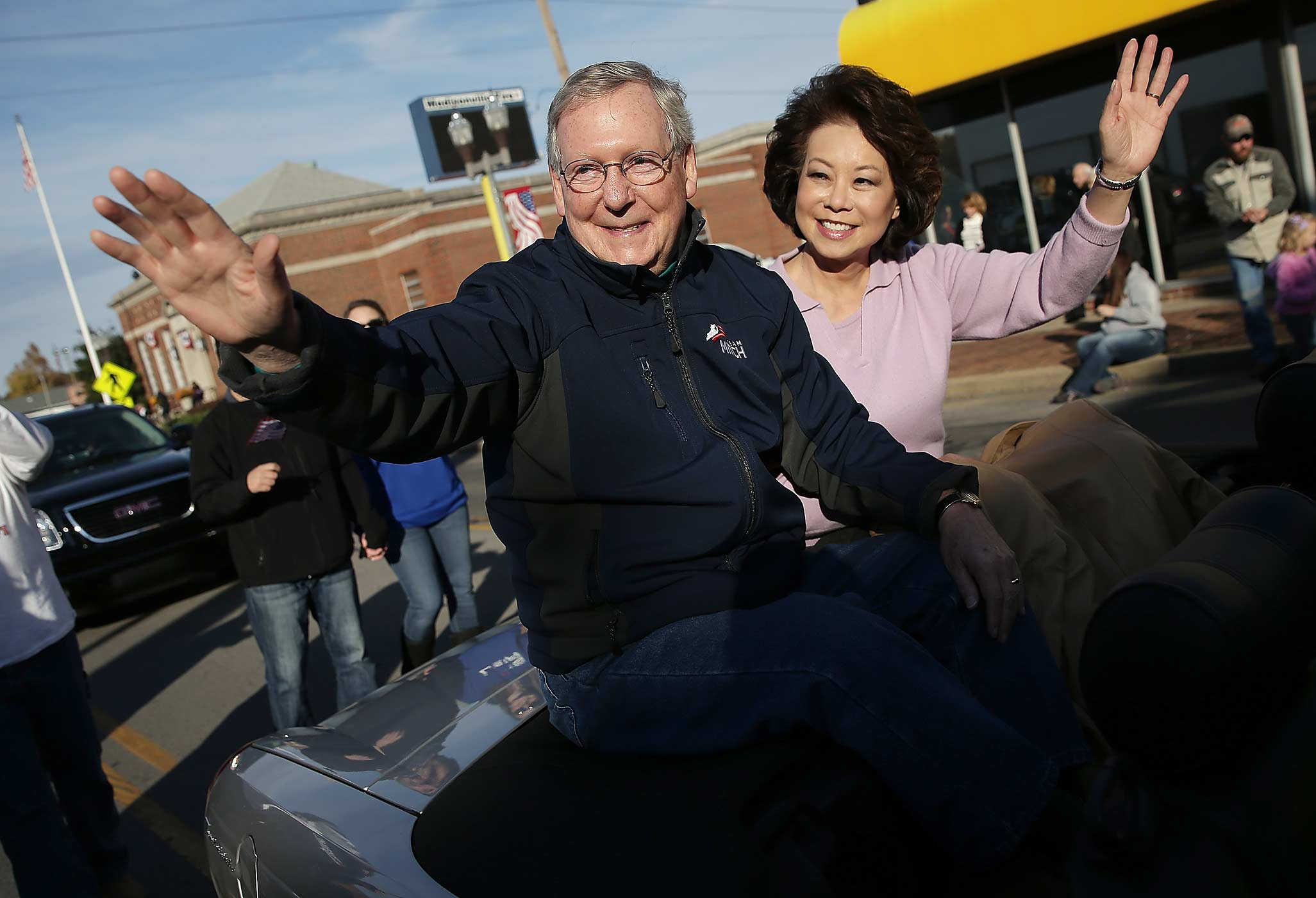 Senate Minority Leader Mitch McConnell waves while riding with his wife Elaine Chao in the Hopkins Country Veterans Day Parade on November 2, 2014 in Madisonville, Kentucky.