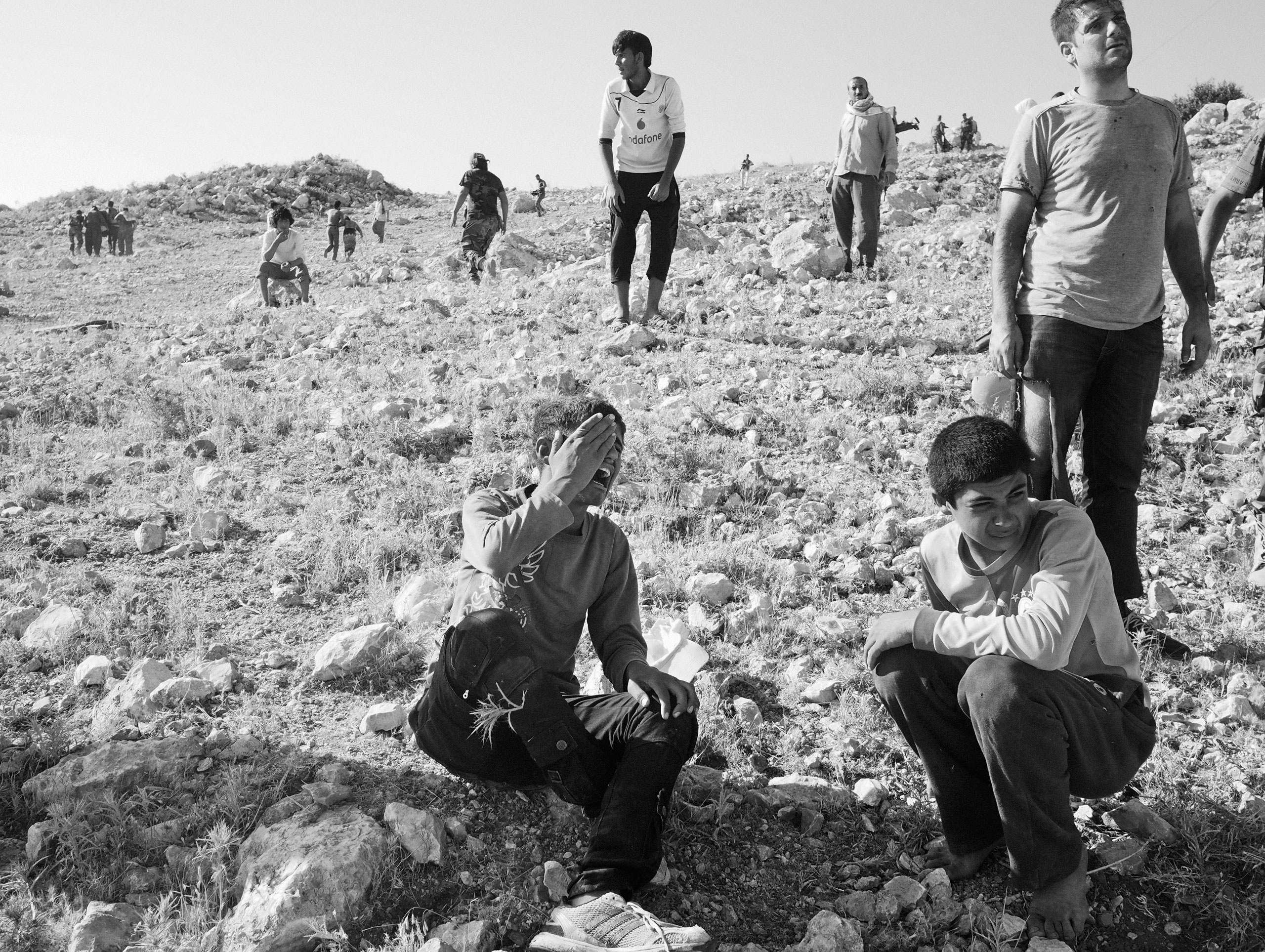 A boy whose mother was onboard the helicopter cries as he does not know her fate. She survived. Sinjar Mountains, Iraq. Aug. 12, 2014.