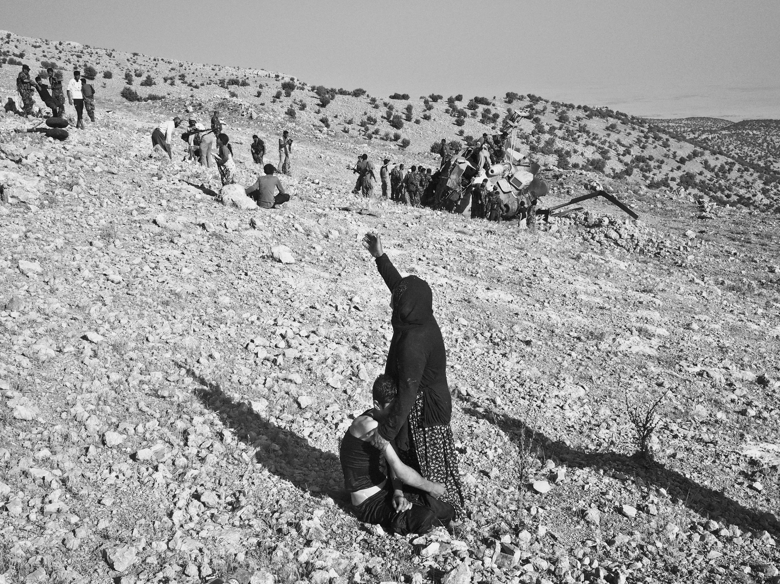 A woman cries for help as she holds on to her wounded son at the crash site of an Iraqi air force helicopter. Sinjar Mountains, Iraq. Aug. 12, 2014.