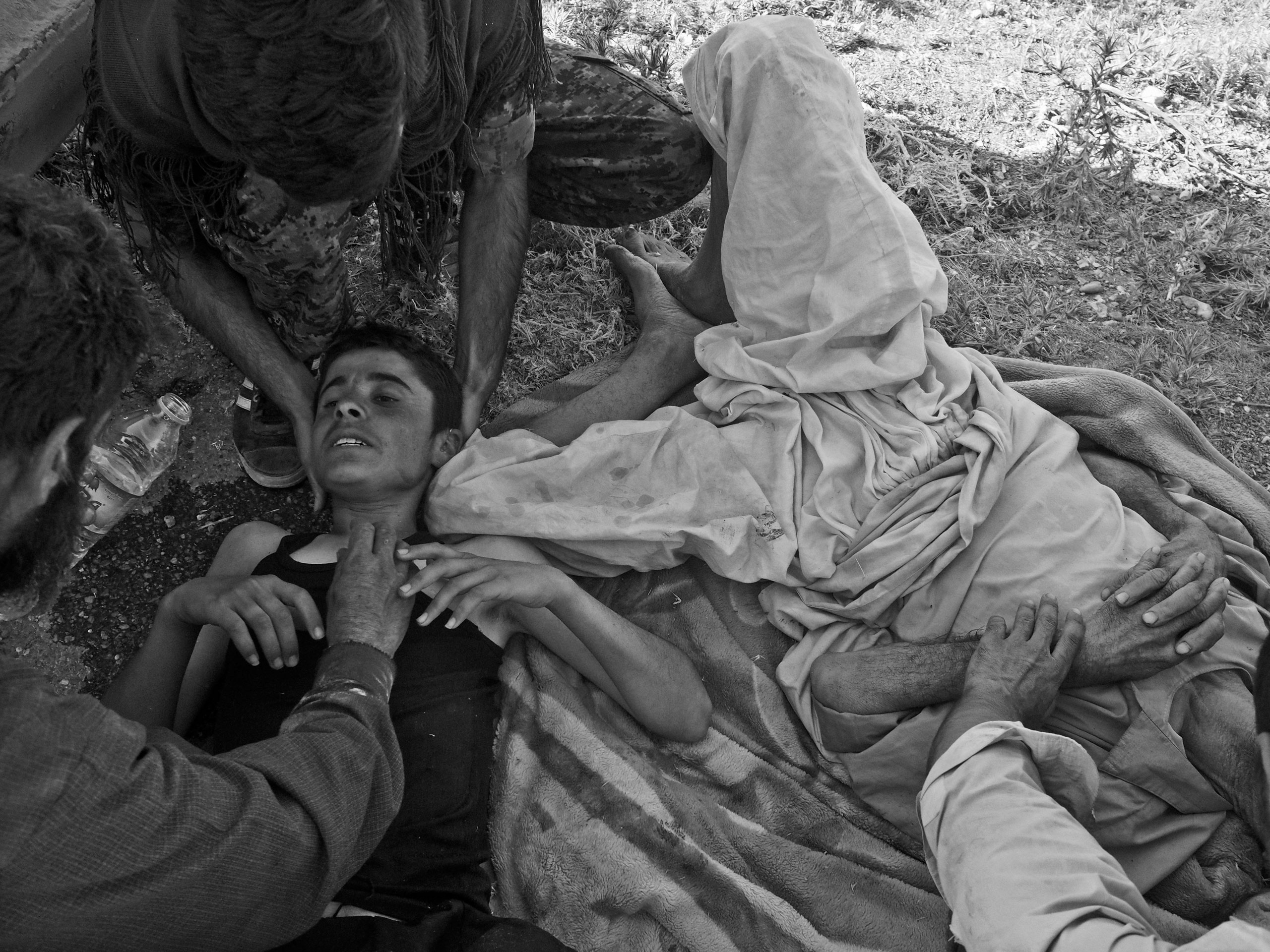 Wounded Yezidi refugees receive care after a helicopter crash. Sinjar Mountains, Iraq. Aug. 12, 2014.