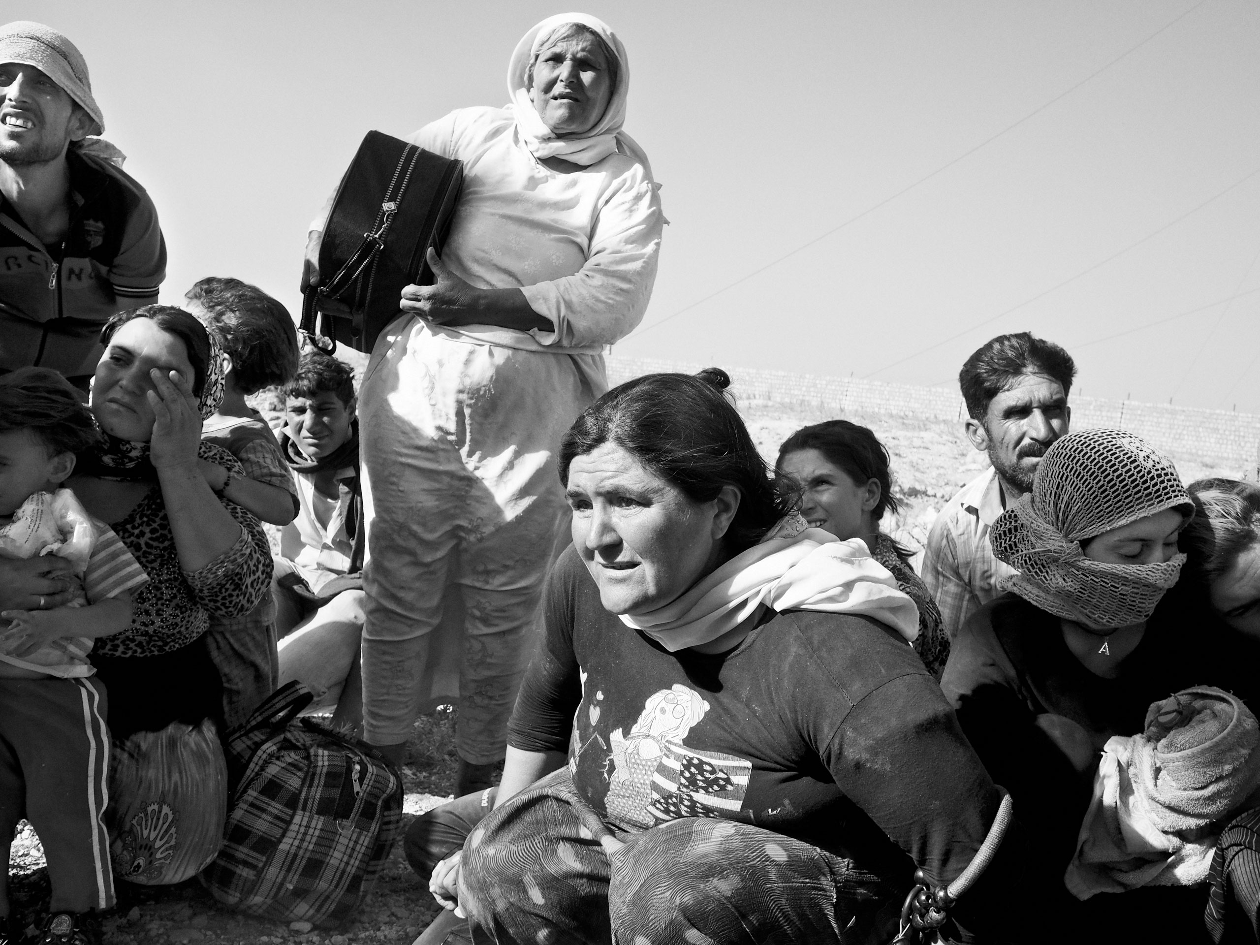 Stranded Yezidi families huddle together as they await to board a rescue helicopter. Sinjar Mountains, Iraq. Aug. 12, 2014.