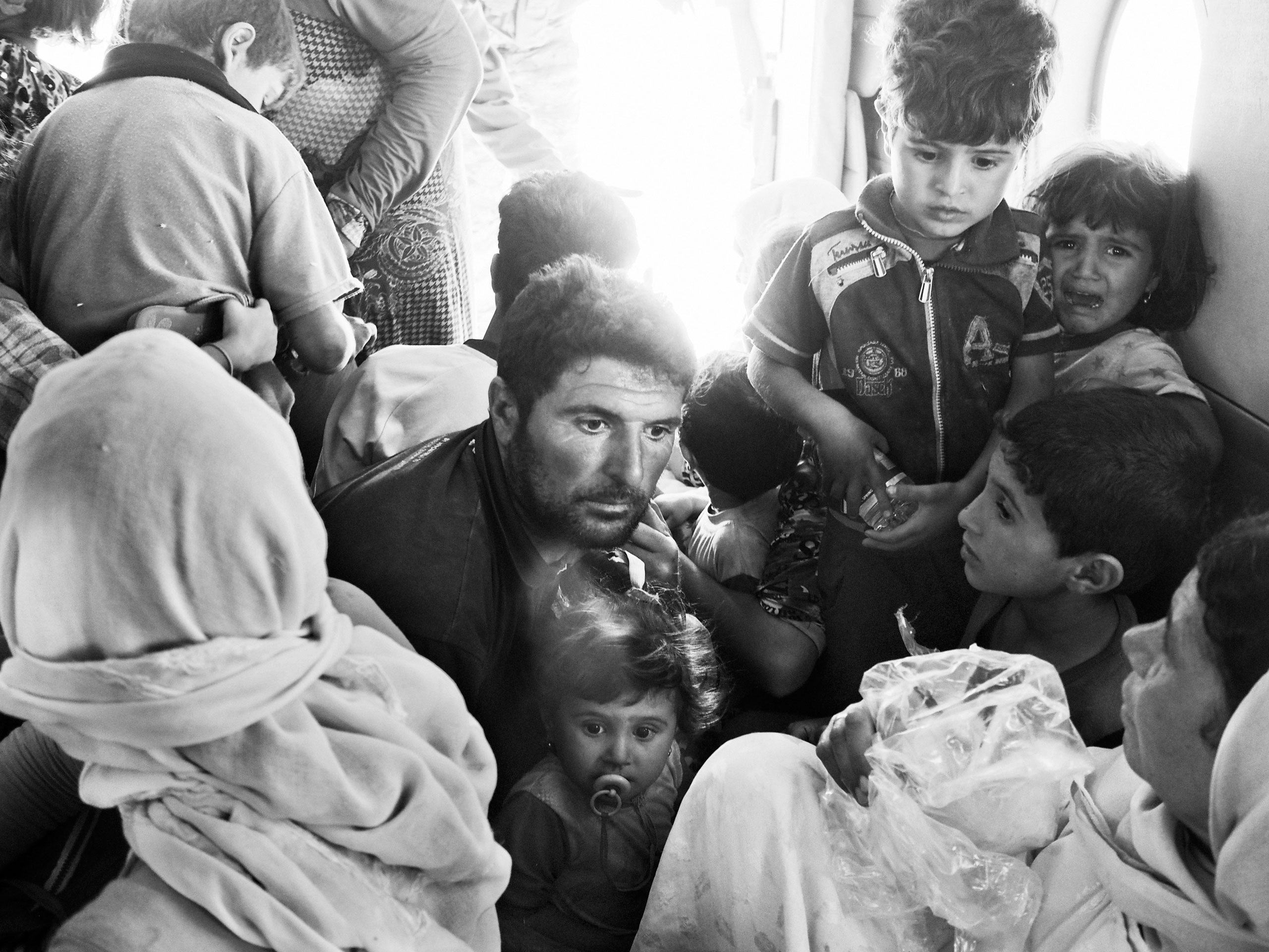 Frightened Yezidi families aboard an Iraqi air force rescue helicopter. Sinjar Mountains, Iraq. Aug. 12, 2014.