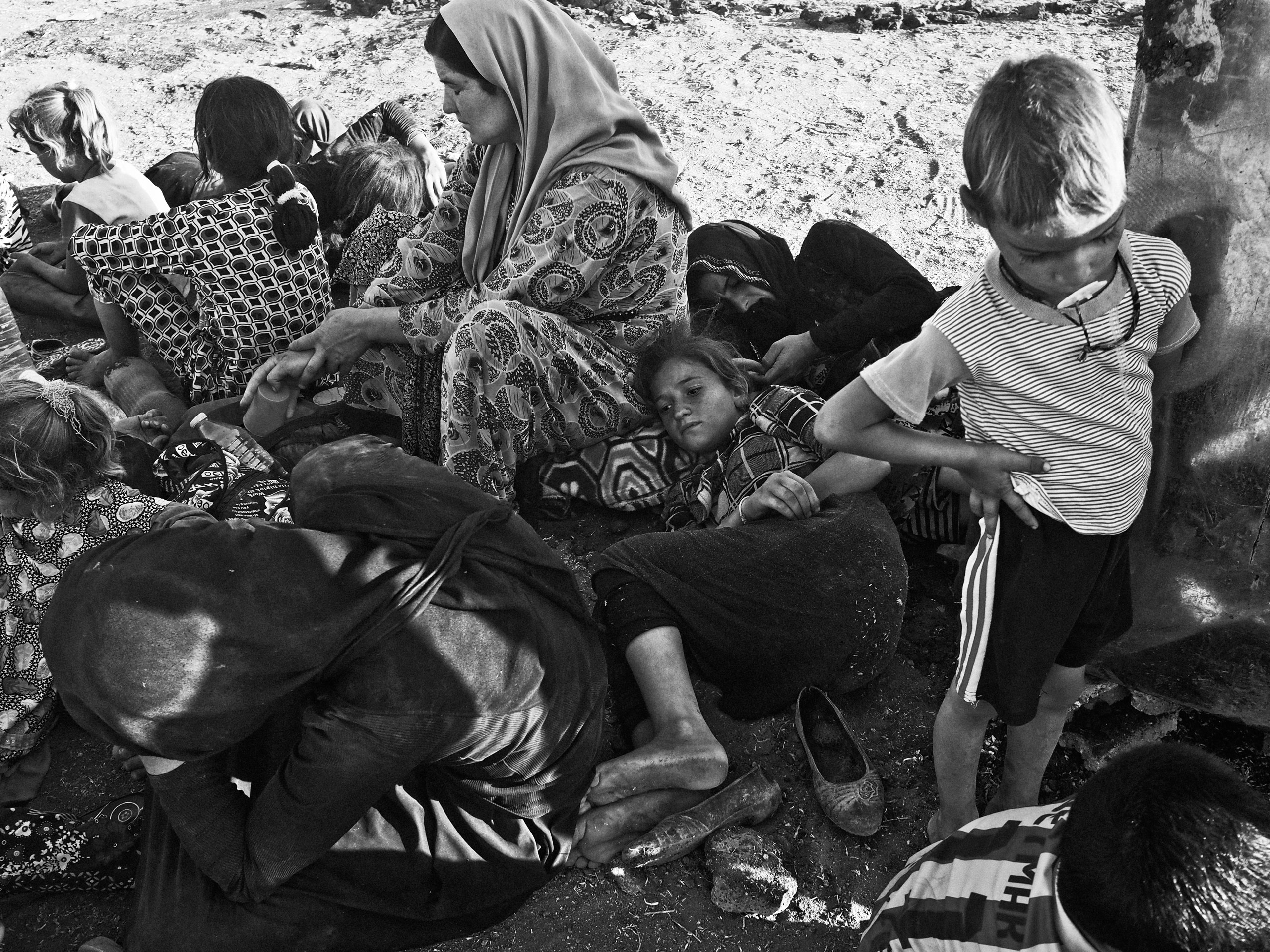 Yezidi women and children from Sinjar, Iraq, rest at a makeshift camp on the outskirts of Derek, a Kurdish-controlled town in Syria that is located at the foot of the Sinjar Mountains. Derek, Syria. Aug. 10, 2014.