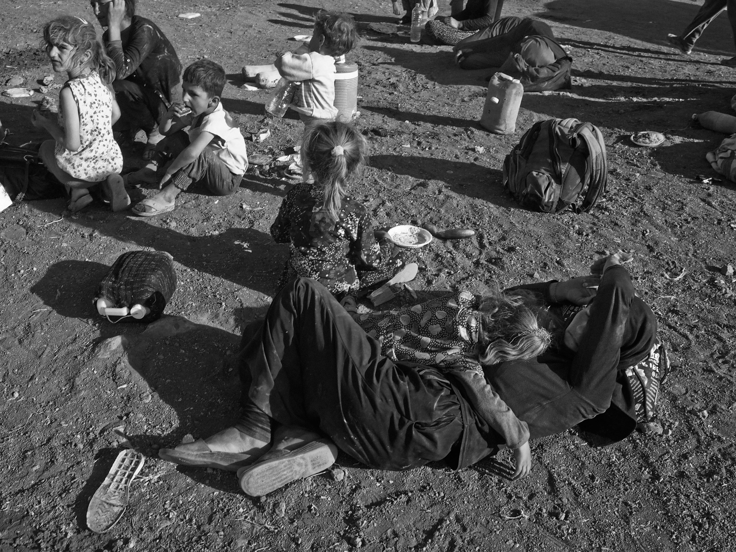Yezidi women and children from Sinjar, Iraq, rest at a makeshift camp on the outskirts of Derek, a Kurdish-controlled town in Syria, shortly after arriving on foot from the Sinjar Mountains where they sought refuge. Aug. 10, 2014.