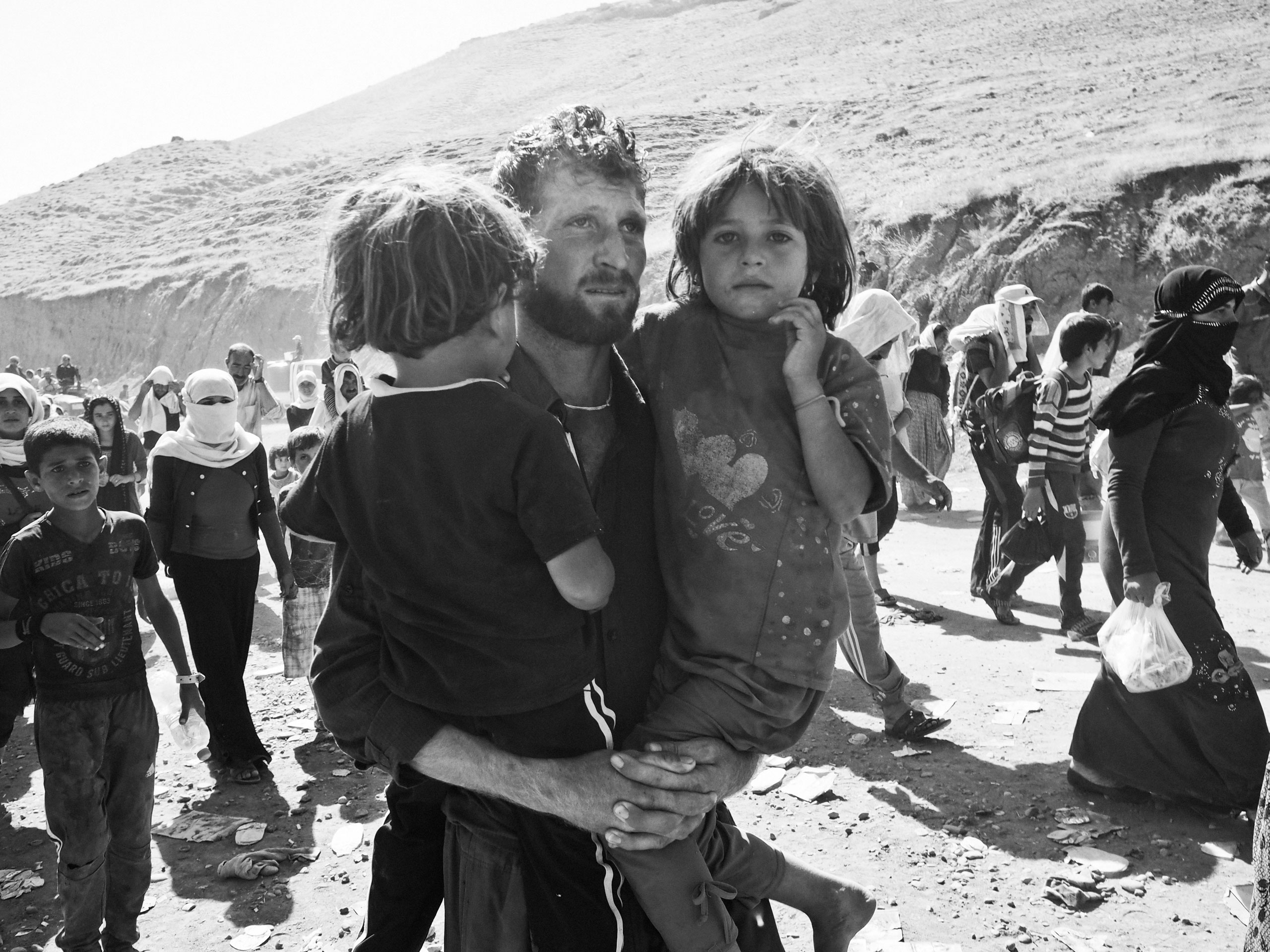 A displaced Yezidi man carries his two daughters as he crosses the border into Kurdish-controlled northern Iraq near the village of Fishkhabur. Iraq. Aug. 10, 2014.