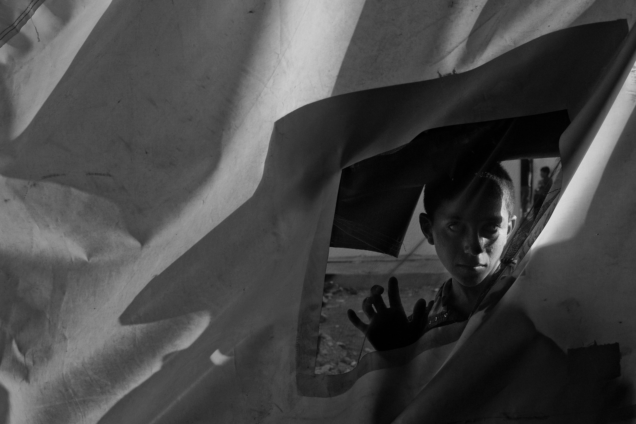 Ahmad Naif, a 14-year-old Yezidi boy from Sinjar, stands behind a tent at a makeshift camp for displaced families near the village of Fishkhabur, in Kurdish-controlled northern Iraq. Aug. 11, 2014.