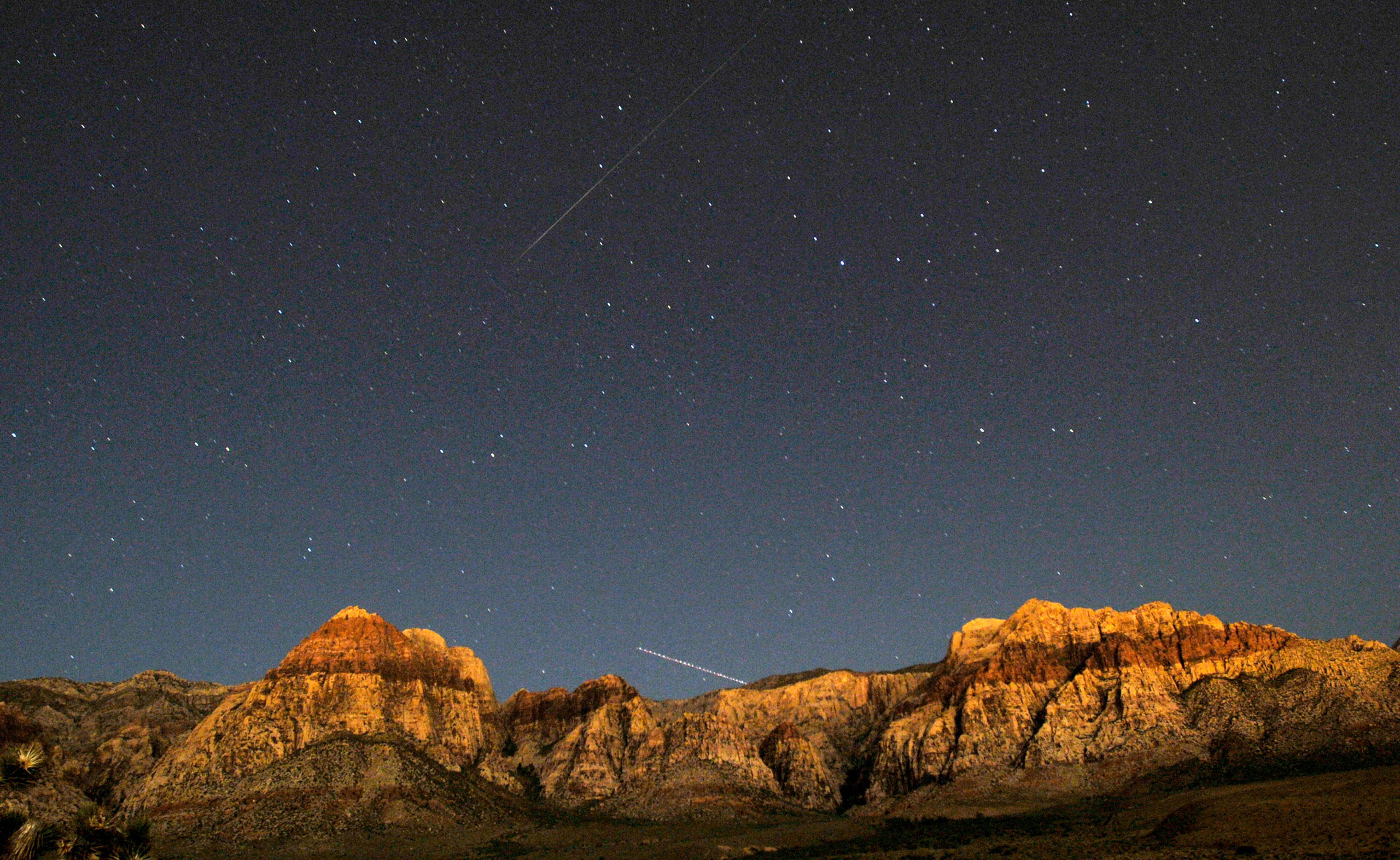 A Perseid meteor (top) and the trail of an jet airplane converge over the cliff walls of Red Rock Canyon outside of Las Vegas on Aug. 11, 2009.