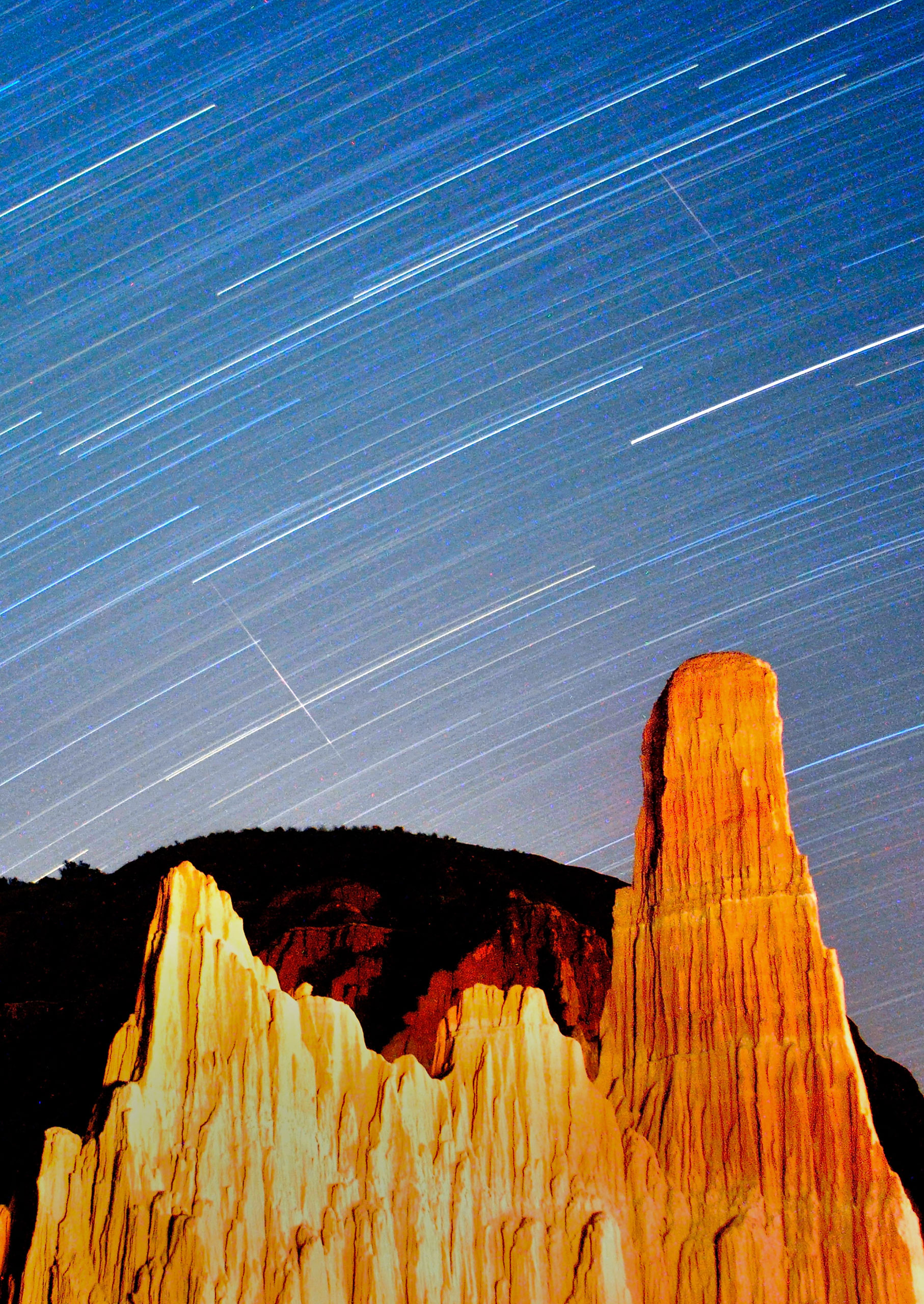 Perseid meteors streak across the sky through star trails over Cathedral Gorge State Park in this long exposure on Aug. 12, 2013.
