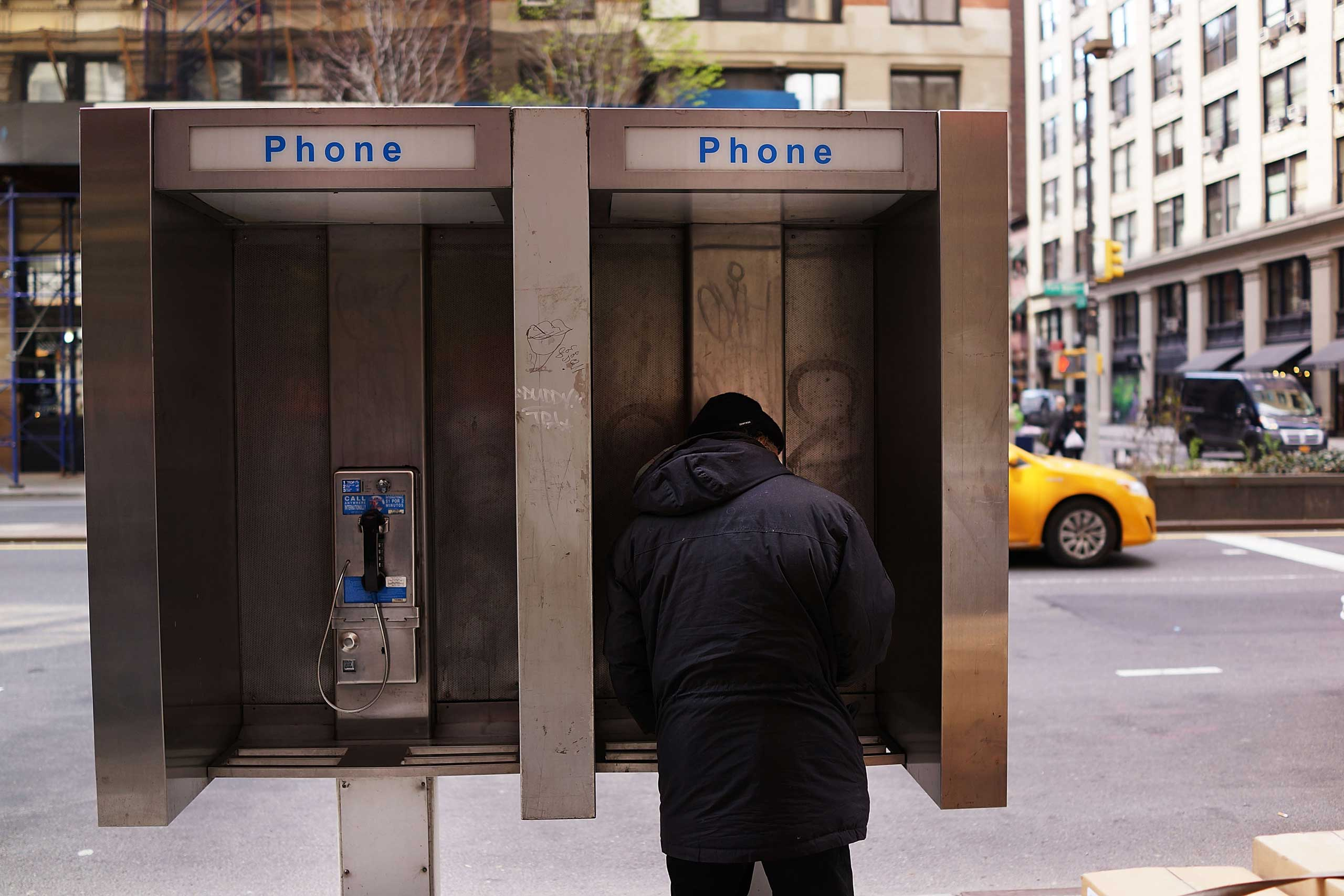 A man stands in a public phone booth on a Manhattan street on May 2, 2014 in New York City.